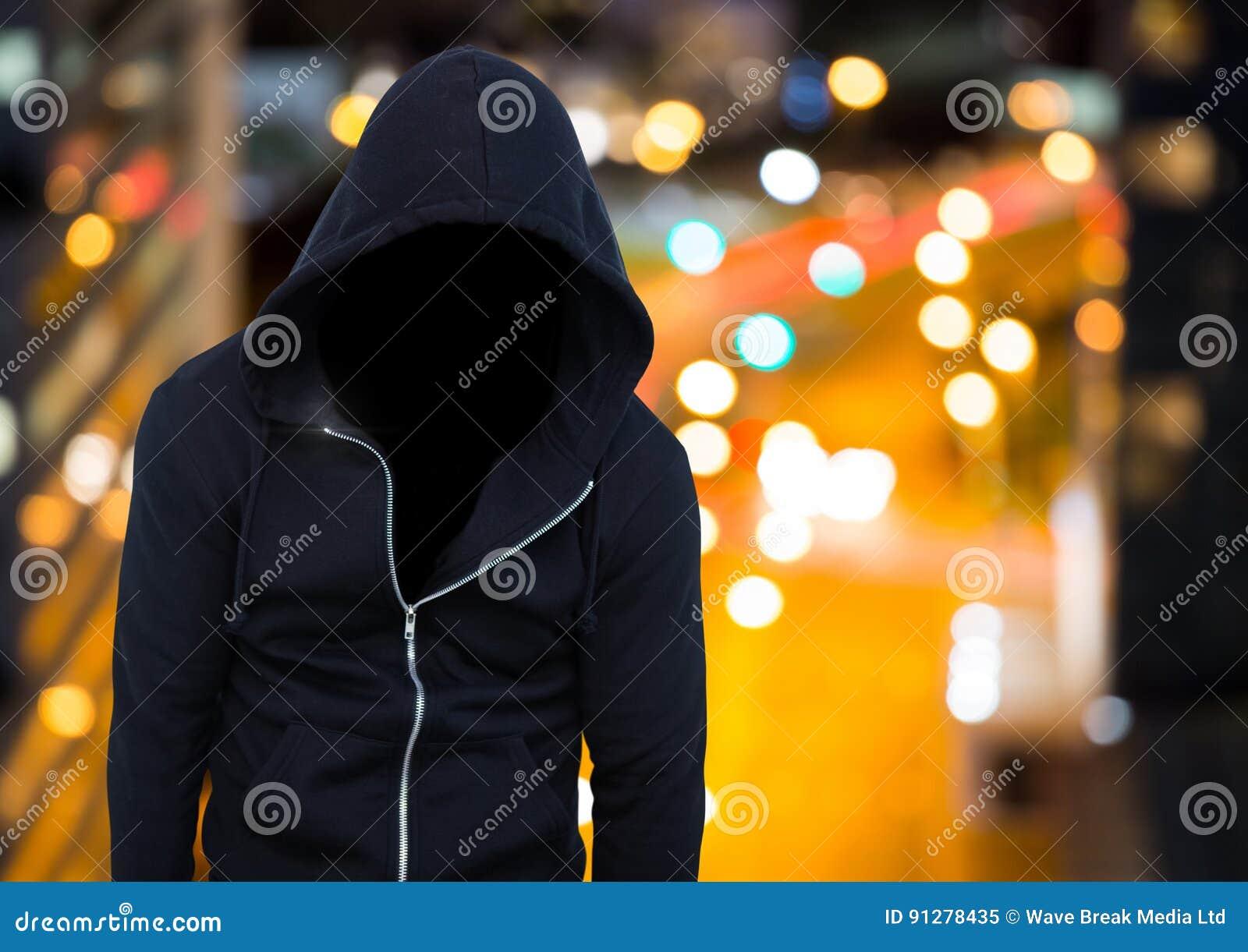 Bärande huv för anonym man framme av nattstaden