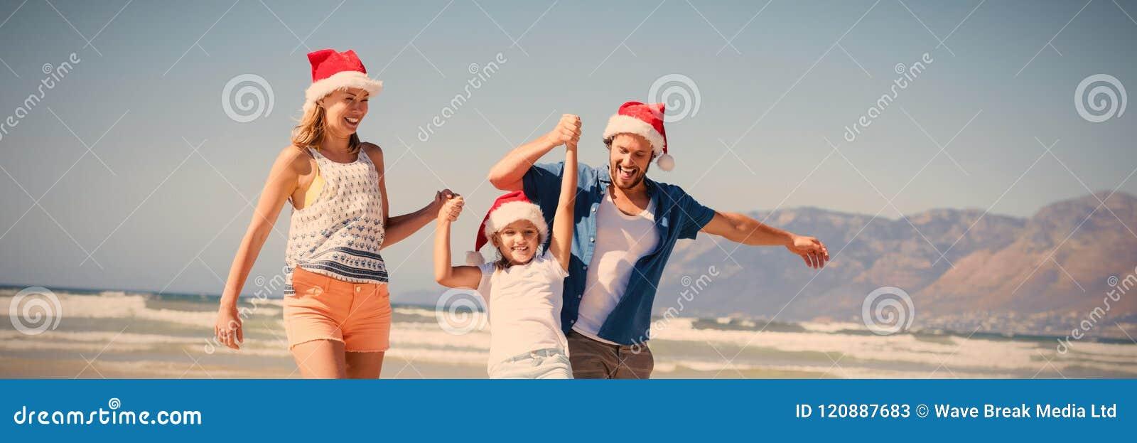 Bärande jultomtenhatt för lycklig familj, medan tycka om på stranden