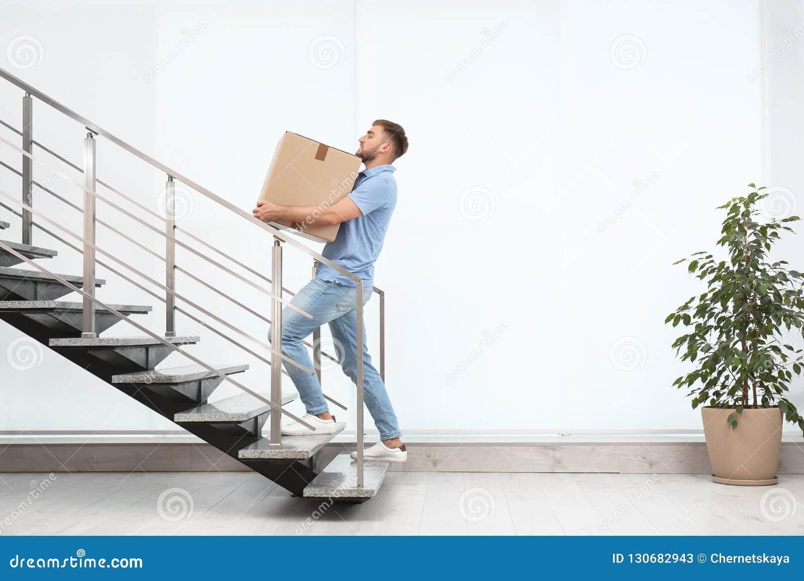 Bärande lådaask för ung man uppför trappan inomhus