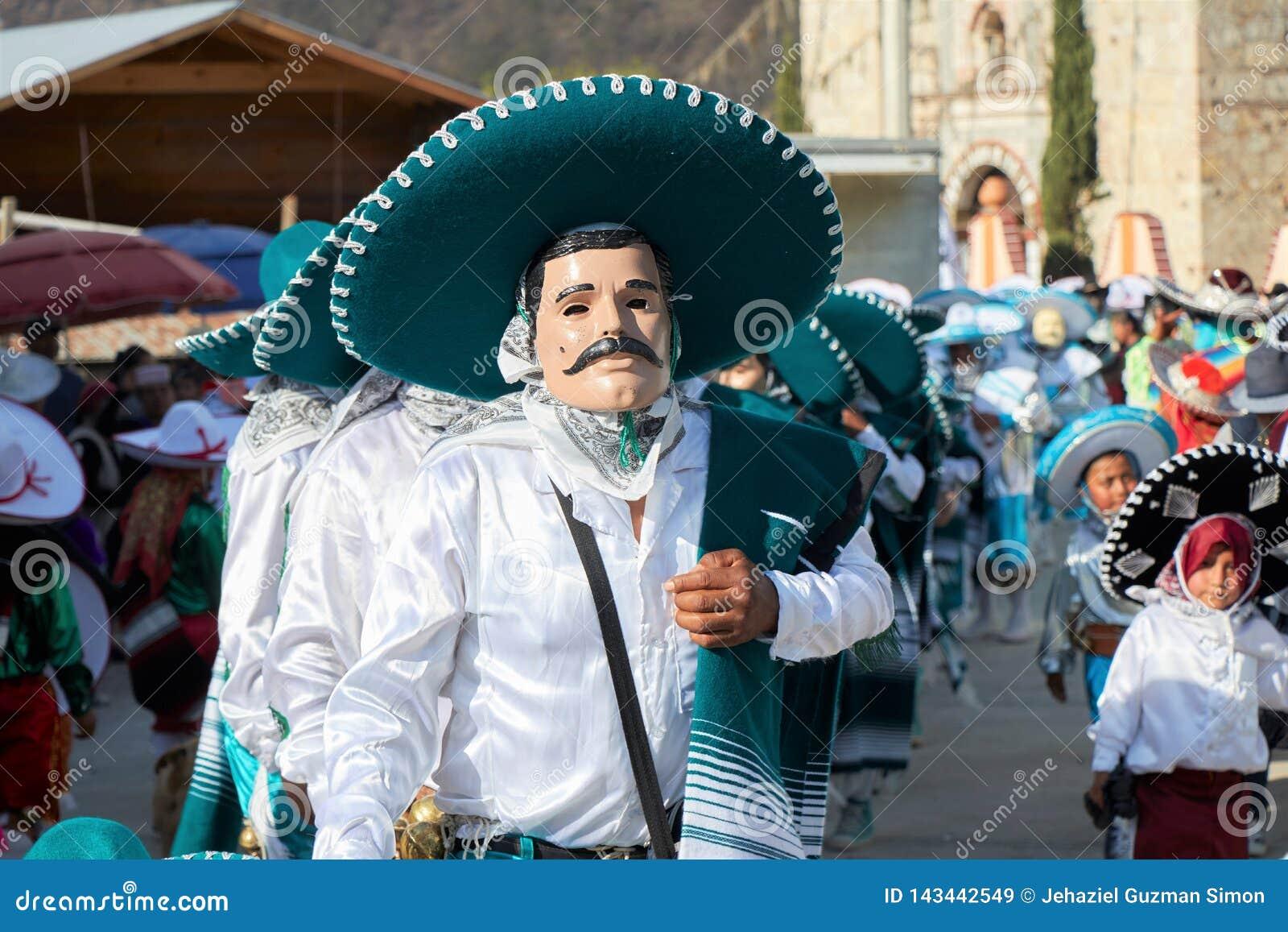 Bärande maskering för person och förställt som mariachien med mörkt - grön hatt under a