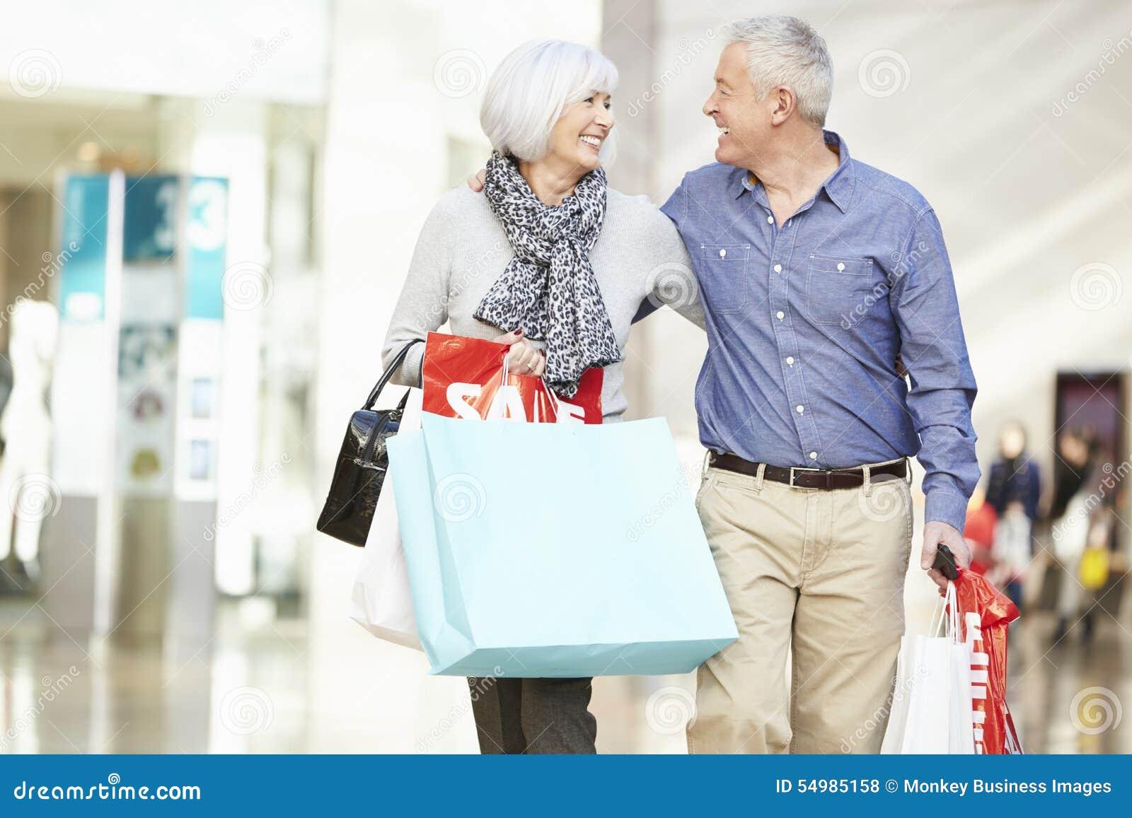 Bärande påsar för lyckliga höga par i shoppinggalleria