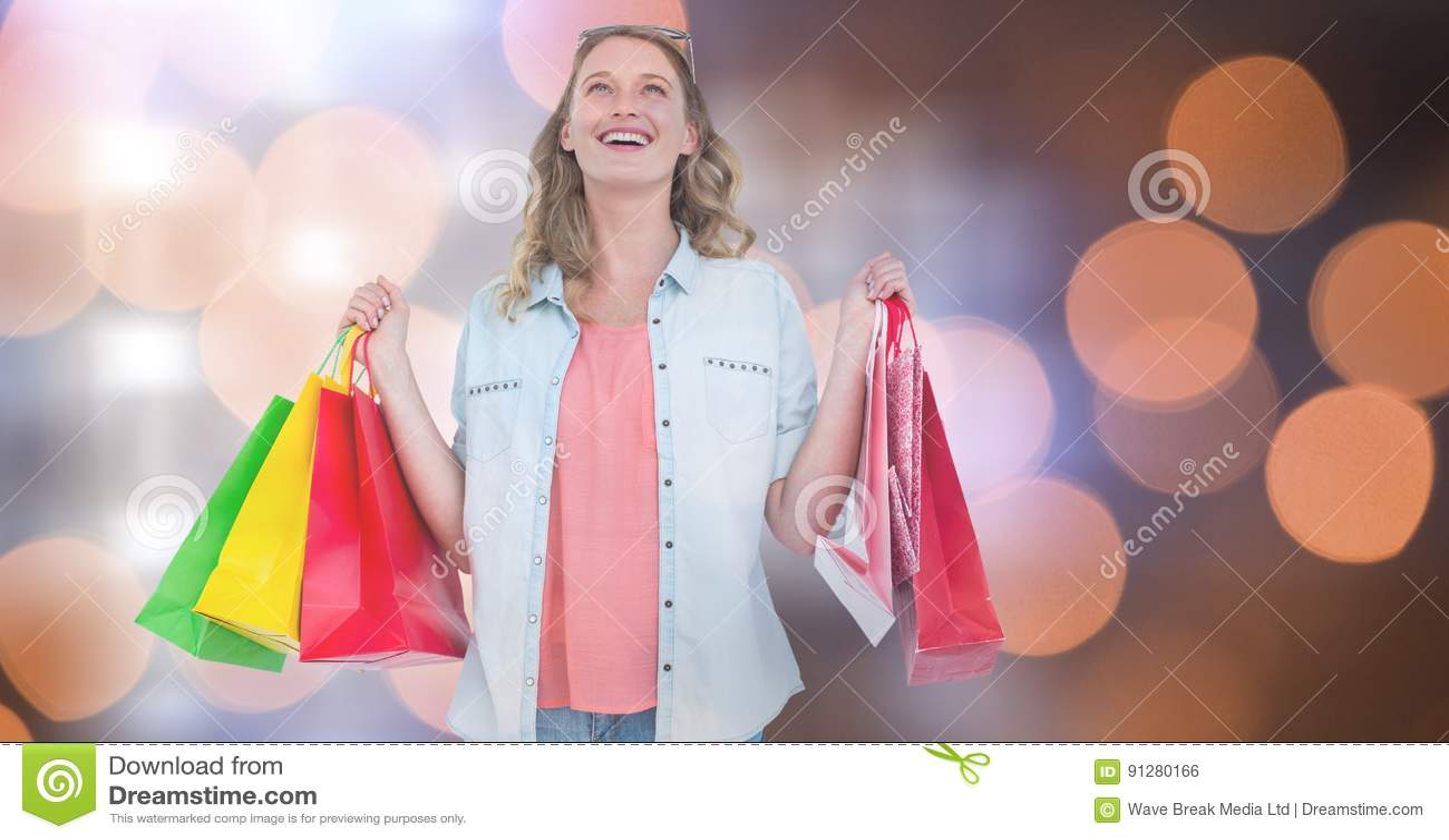 Bärande shoppingpåsar för gladlynt kvinna över bokeh
