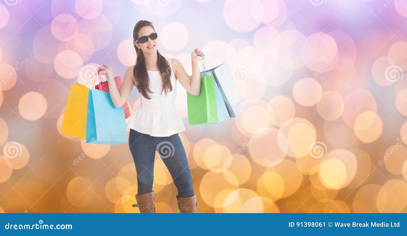 Bärande shoppingpåsar för trendig kvinna över bokeh