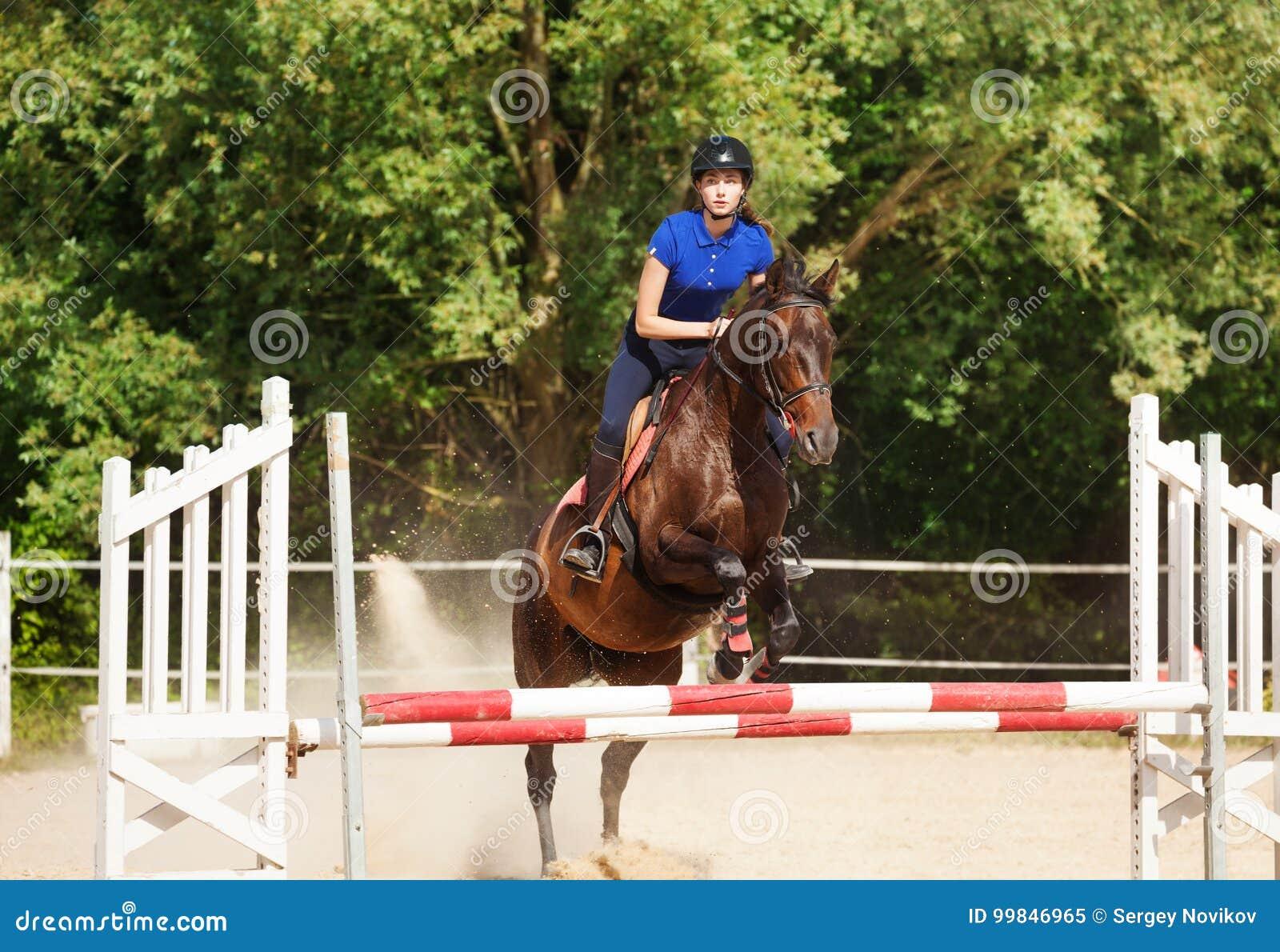 Bärande skicklig ryttarinna för banhoppninghäst under utbildning