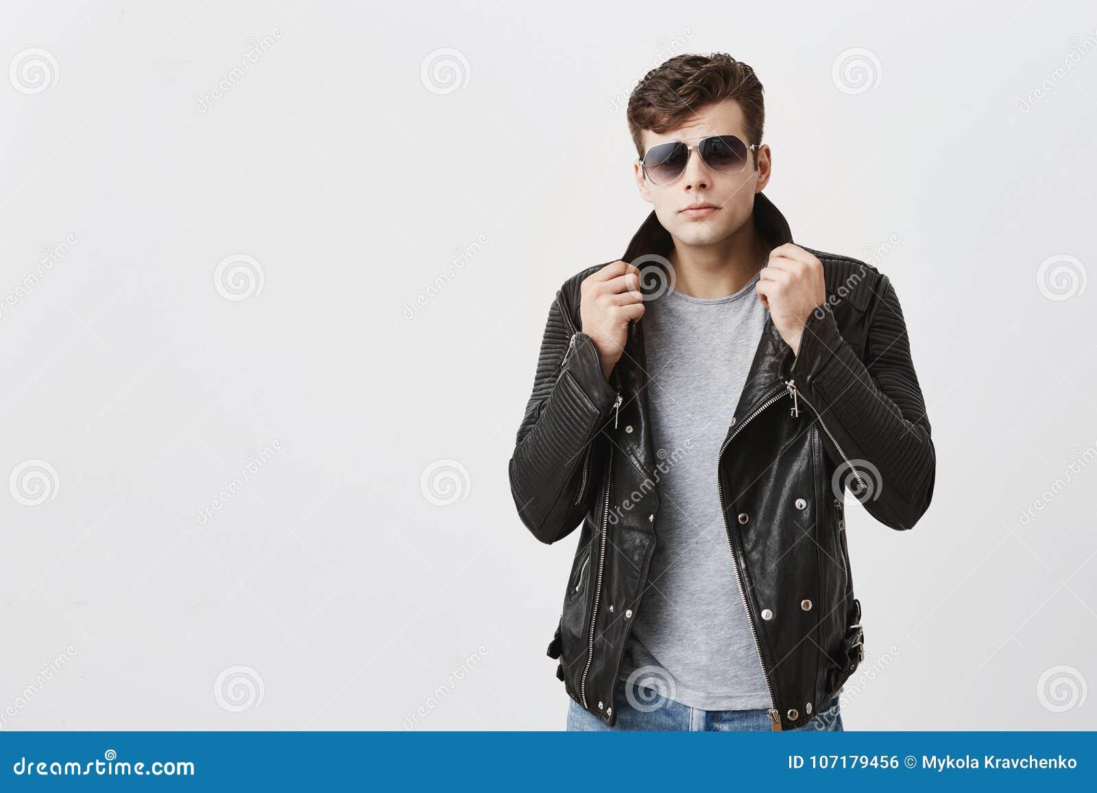 Bärande solglasögon för muskulös säker man som inomhus poserar Attraktiv stilig grabb med moderiktig frisyr i svart läder
