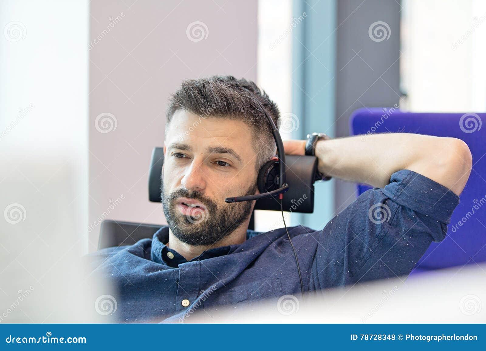 Bärande telefonhörlurar med mikrofon för mitt- vuxen affärsman i regeringsställning