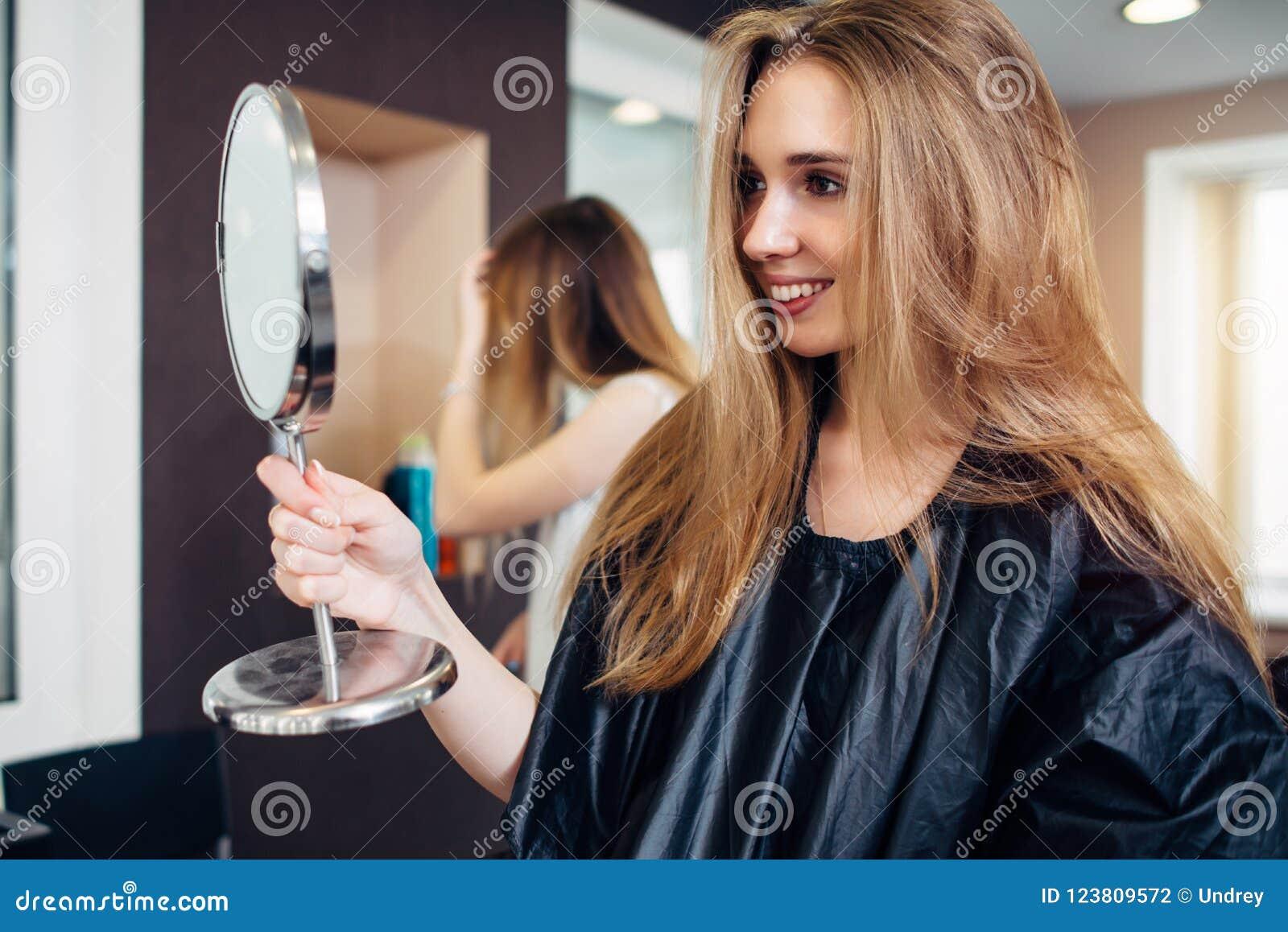 Bärande udde för ung kvinnlig kund som rymmer en makeupspegel som ser och ler i skönhetsalongen som tillfredsställs med smink