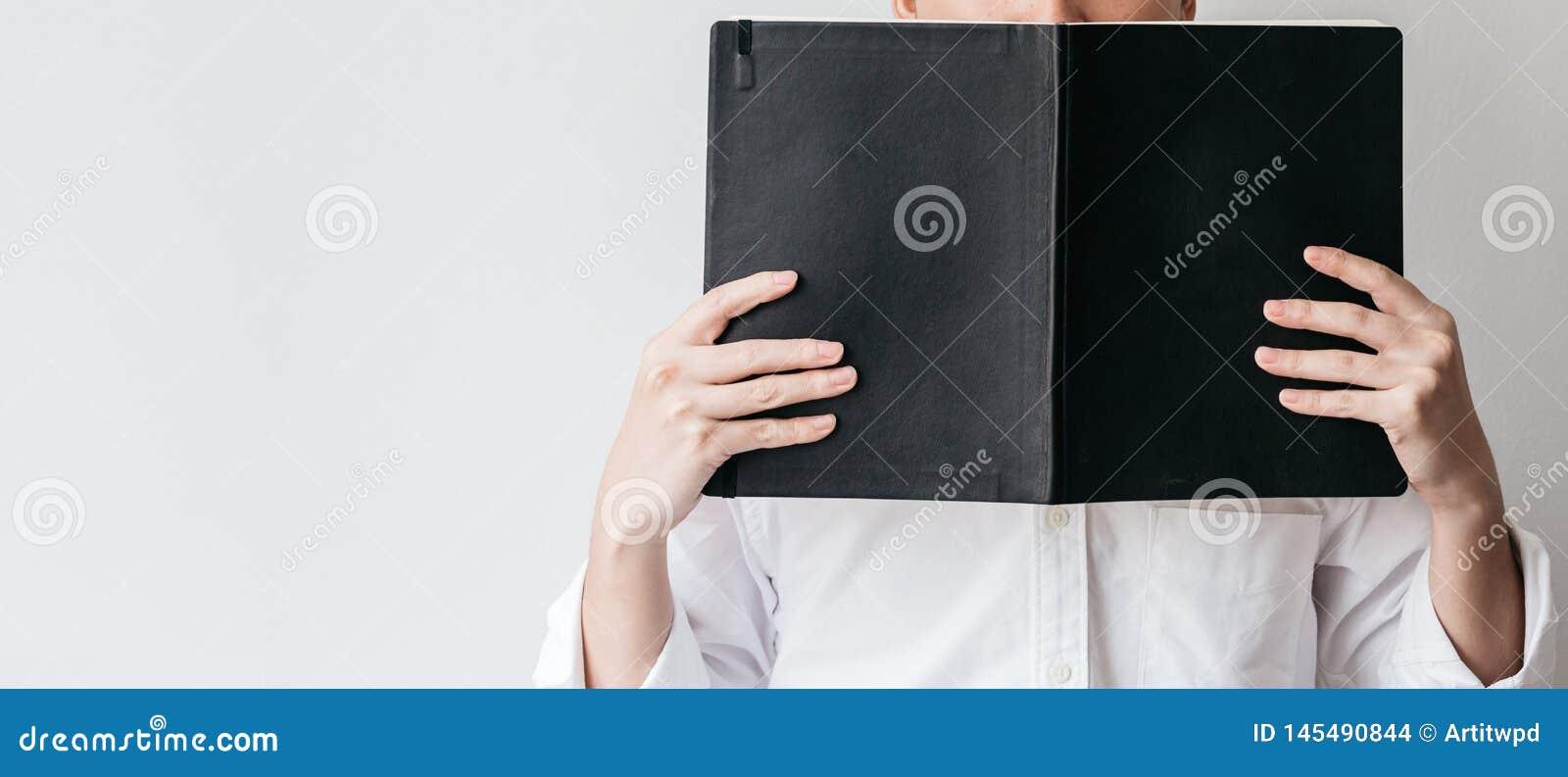 B?rande vit skjorta f?r man och rymma en svart r?kningsbok framme av honom p? r?tsidan med kopieringsutrymme