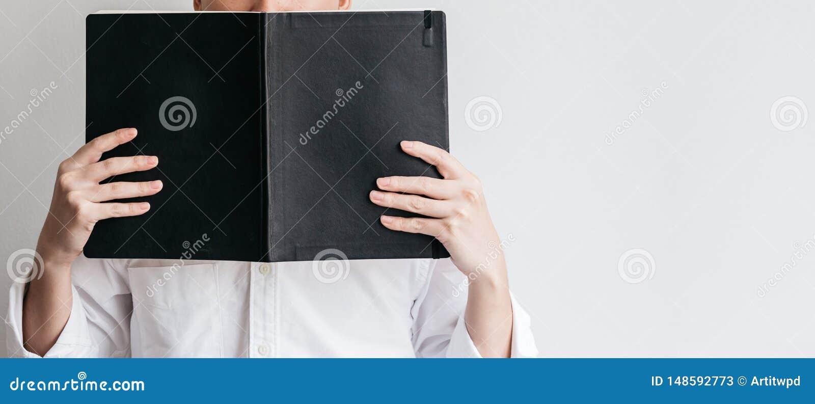 B?rande vit skjorta f?r man och rymma en svart r?kningsbok framme av honom p? v?nstra sidan med kopieringsutrymme