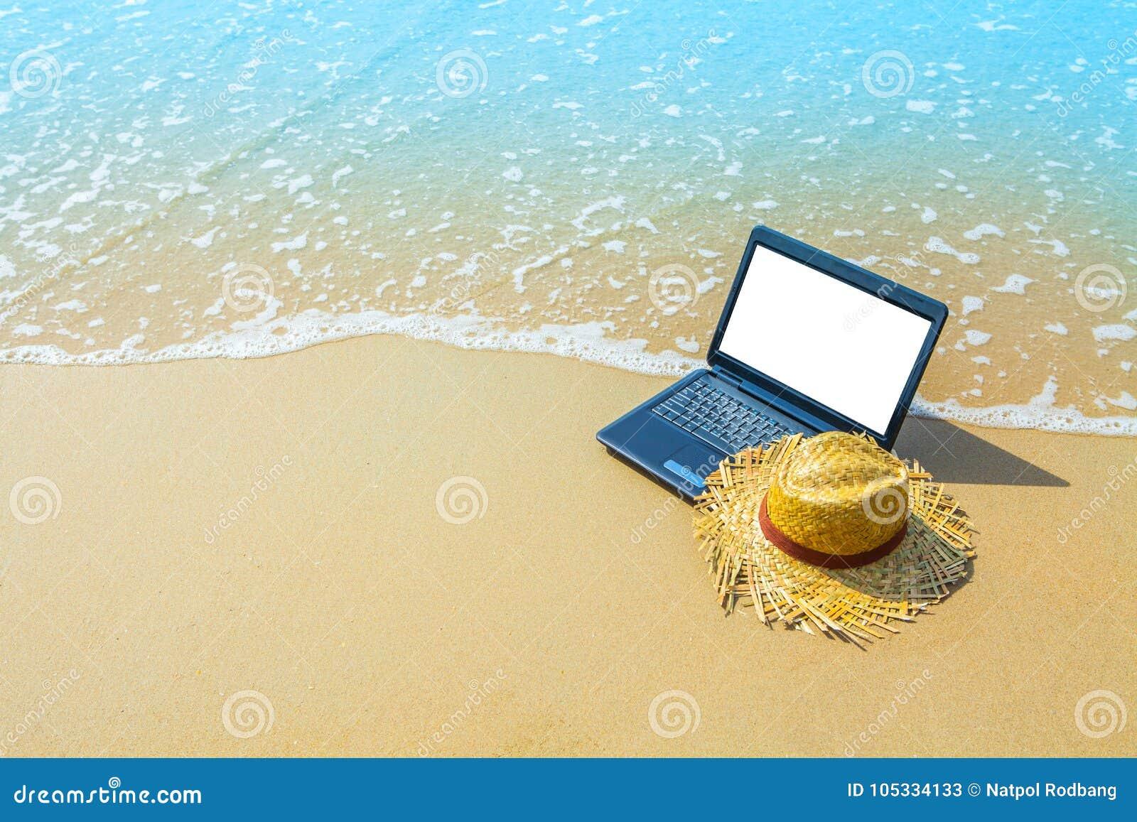 Bärbar dator- eller datoranteckningsbok på havsstranden och vågen - affärstra