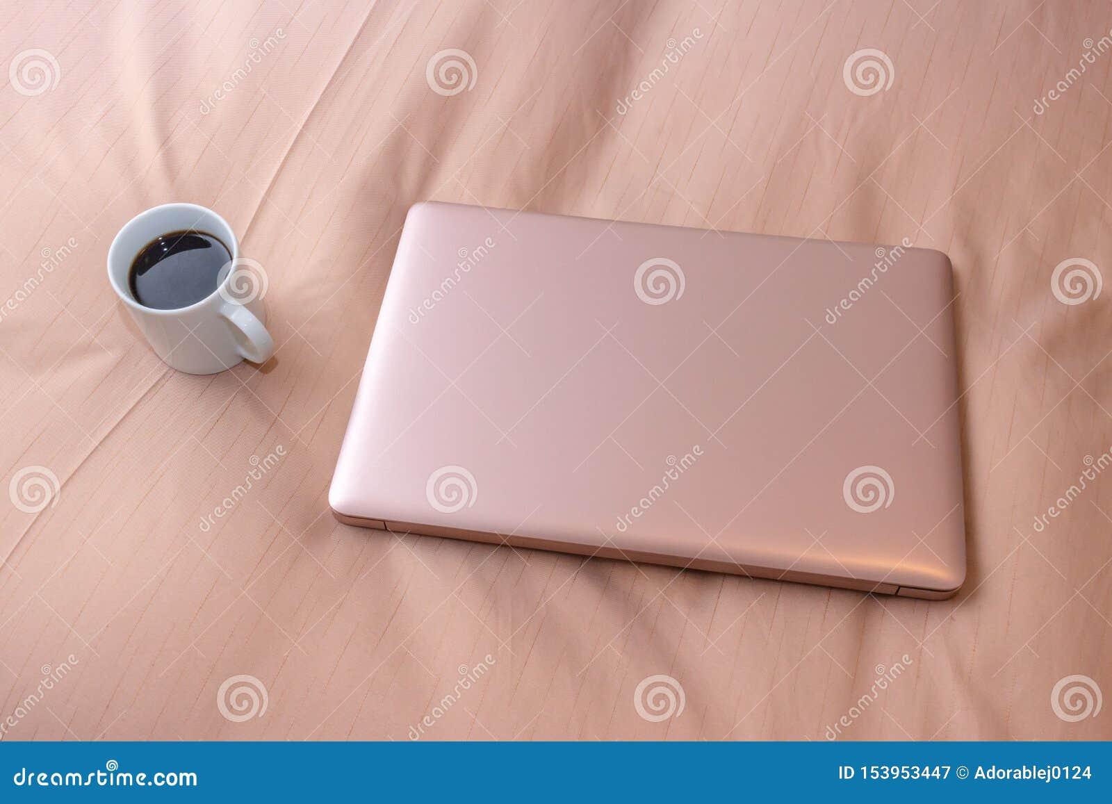 Bärbar dator och en kopp kaffe på sängen, affärstur
