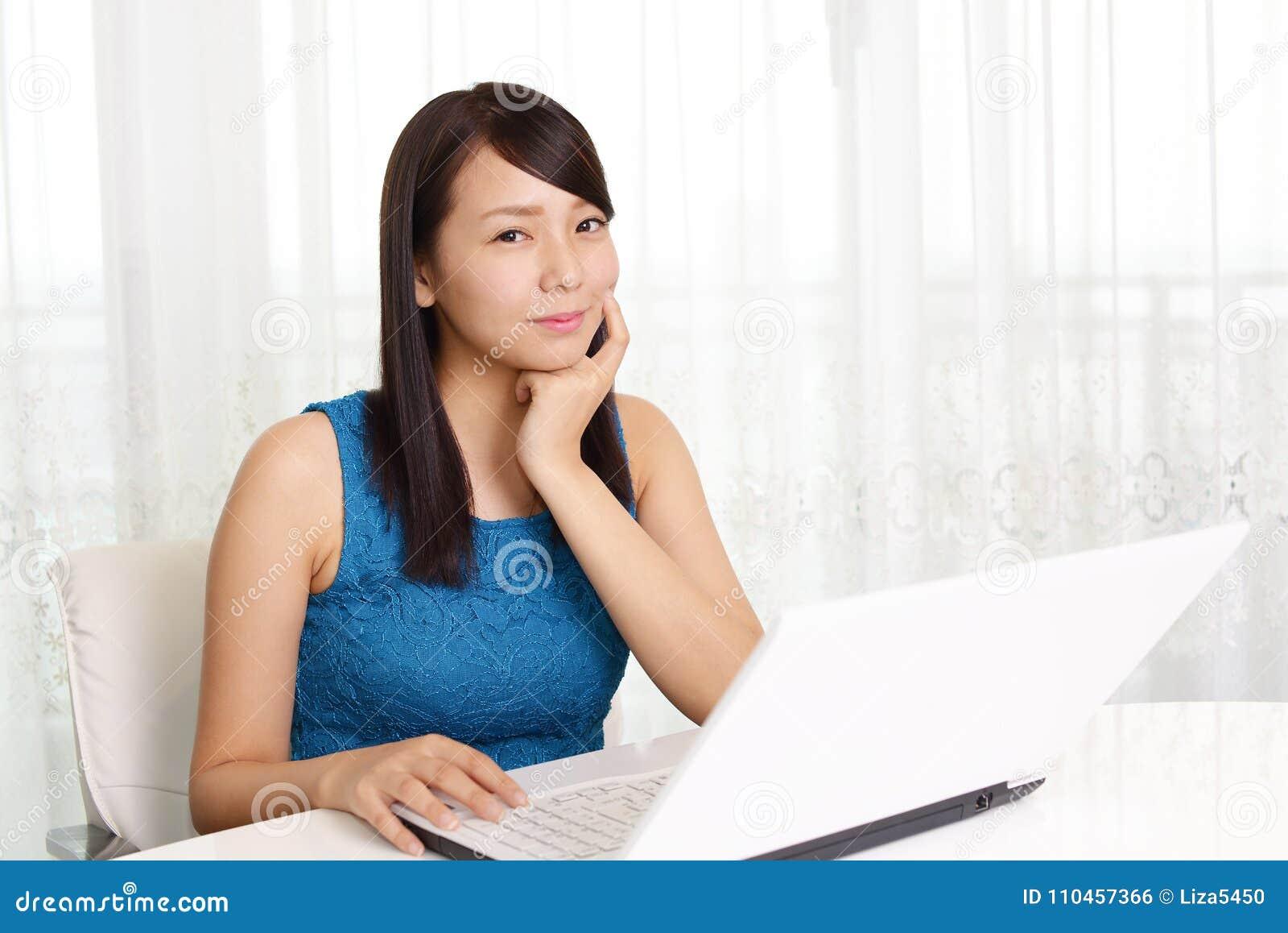 Bärbar dator som ler genom att använda kvinnan