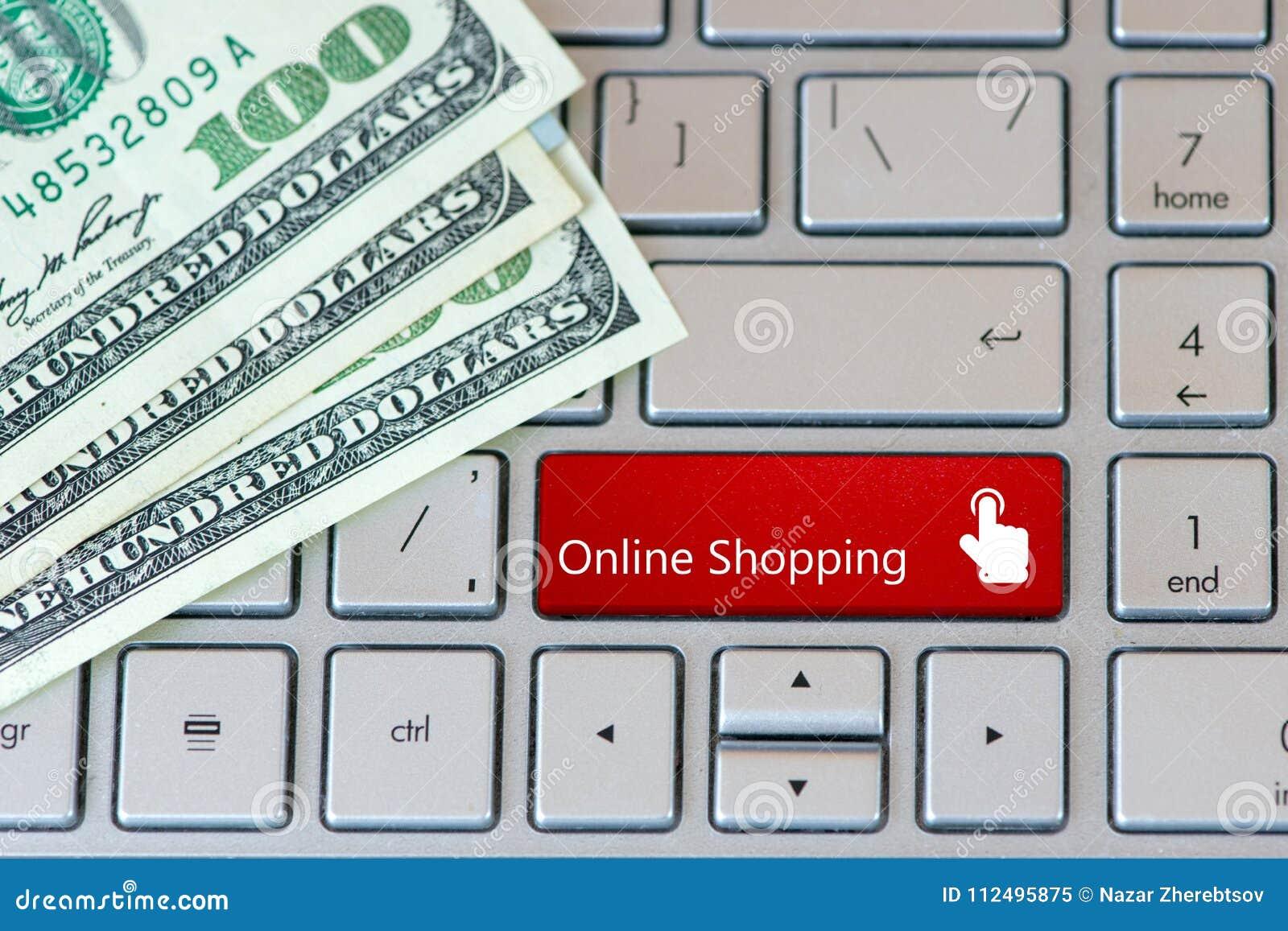 Bärbar datortangentbord med dollarsedlar och den röda knappen - online-shopping
