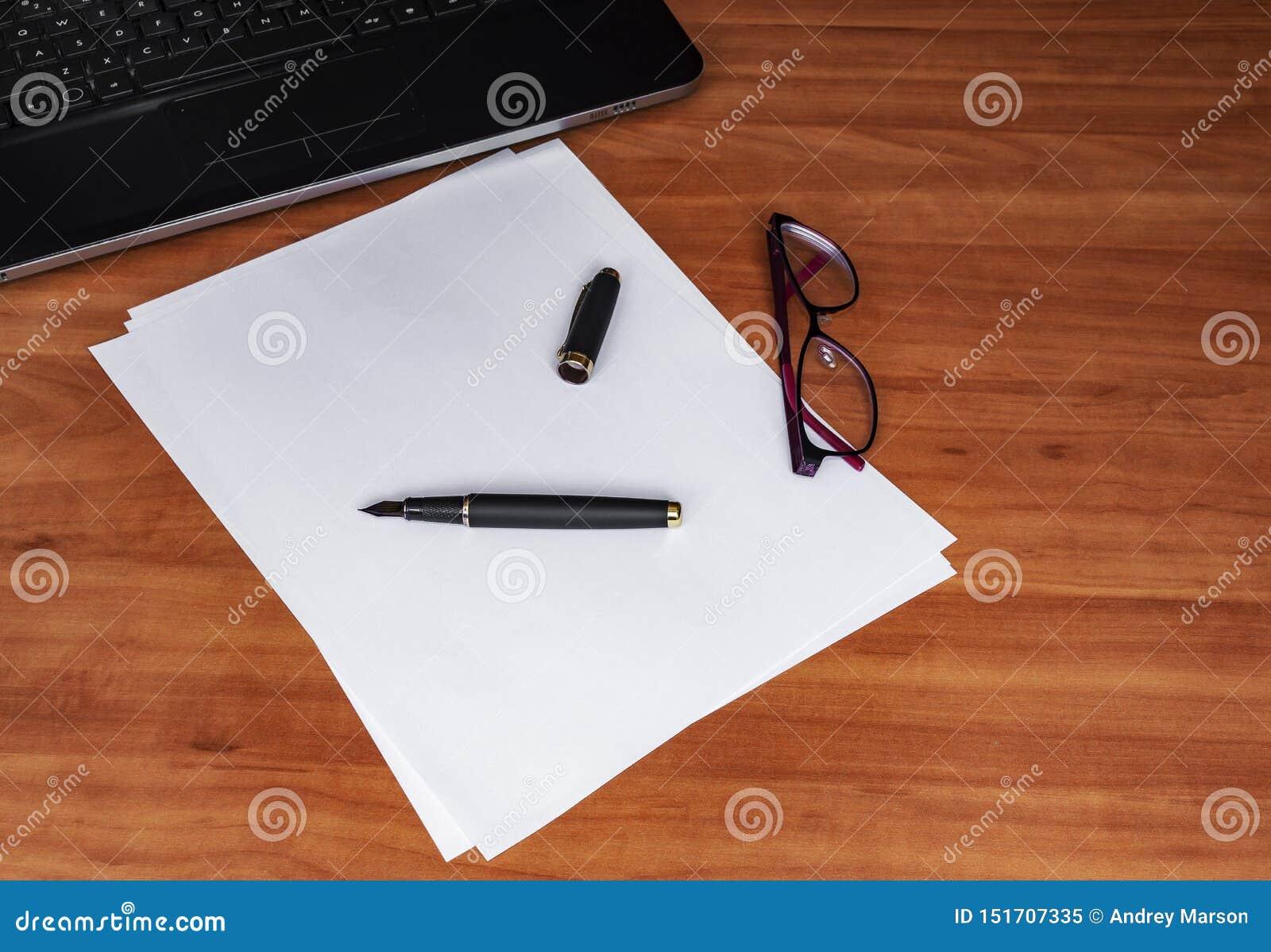 Bärbar datortangentbord, vitbok, bläckpenna och exponeringsglas på en trätabell Tomt utrymme för din kopieringstext