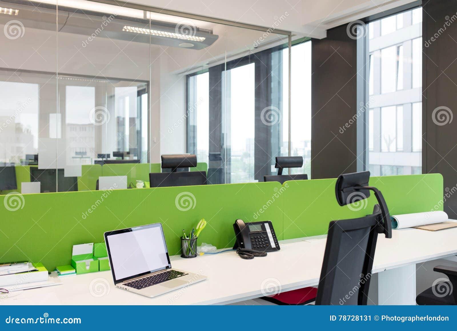 Bärbara datorn och landlinen ringer på skrivbordet på kontoret