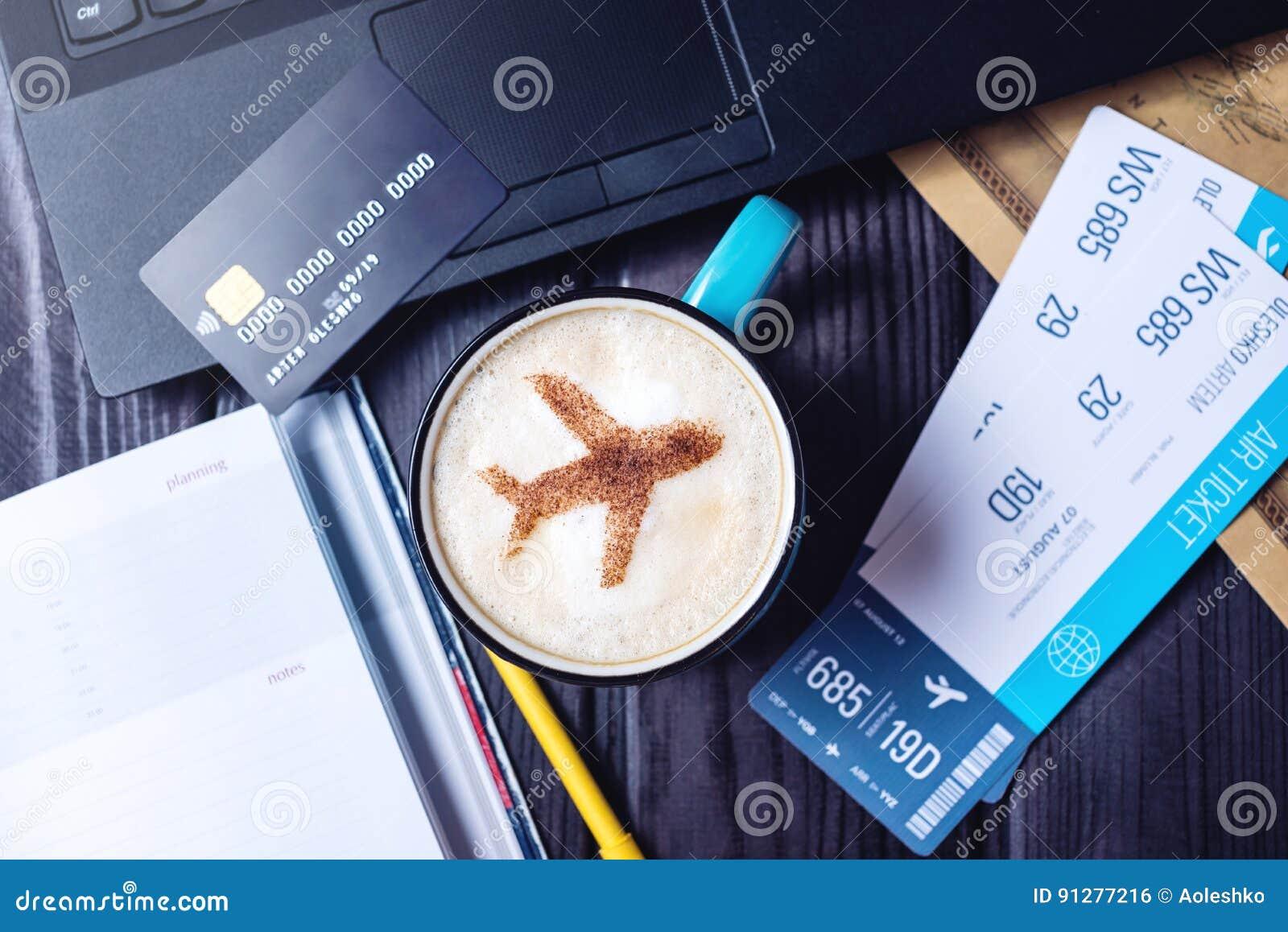 Bärbara datorn plana biljetter, kaffe, kreditkort ligger på tabellen