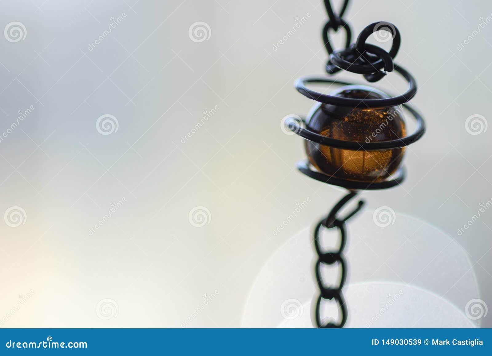 Bärnstensfärgad coloreed exponeringsglaspärla i sprial metall som ställer in med neutral bakgrund