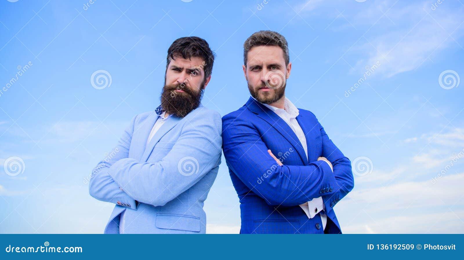 Bärtige Geschäftsleute, die sicher aufwerfen Geschäftsleute stehen Hintergrund des blauen Himmels Vervollkommnen Sie ausführlich
