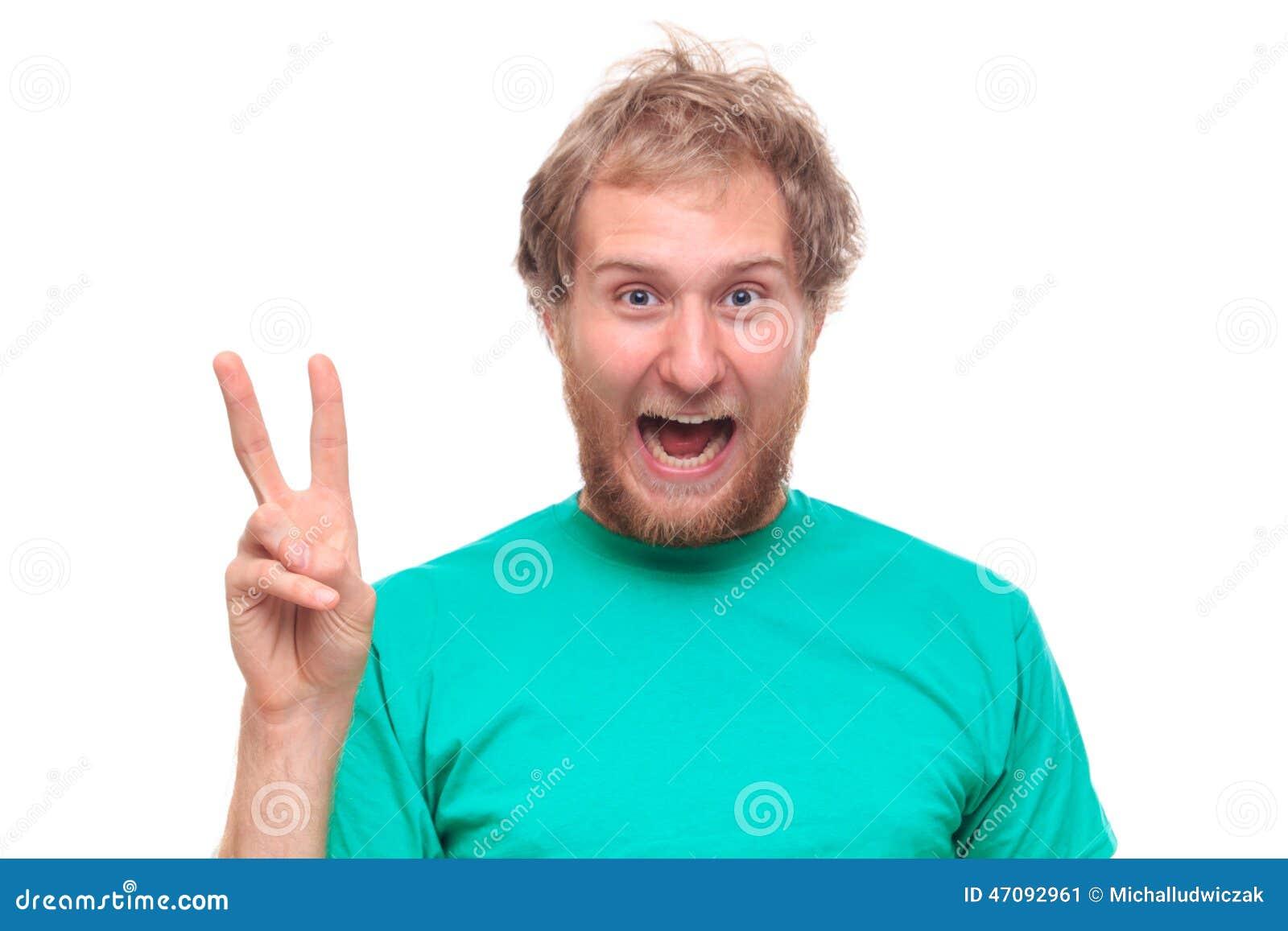 Bärtiger glücklicher Mann, der Siegeszeichen zeigt