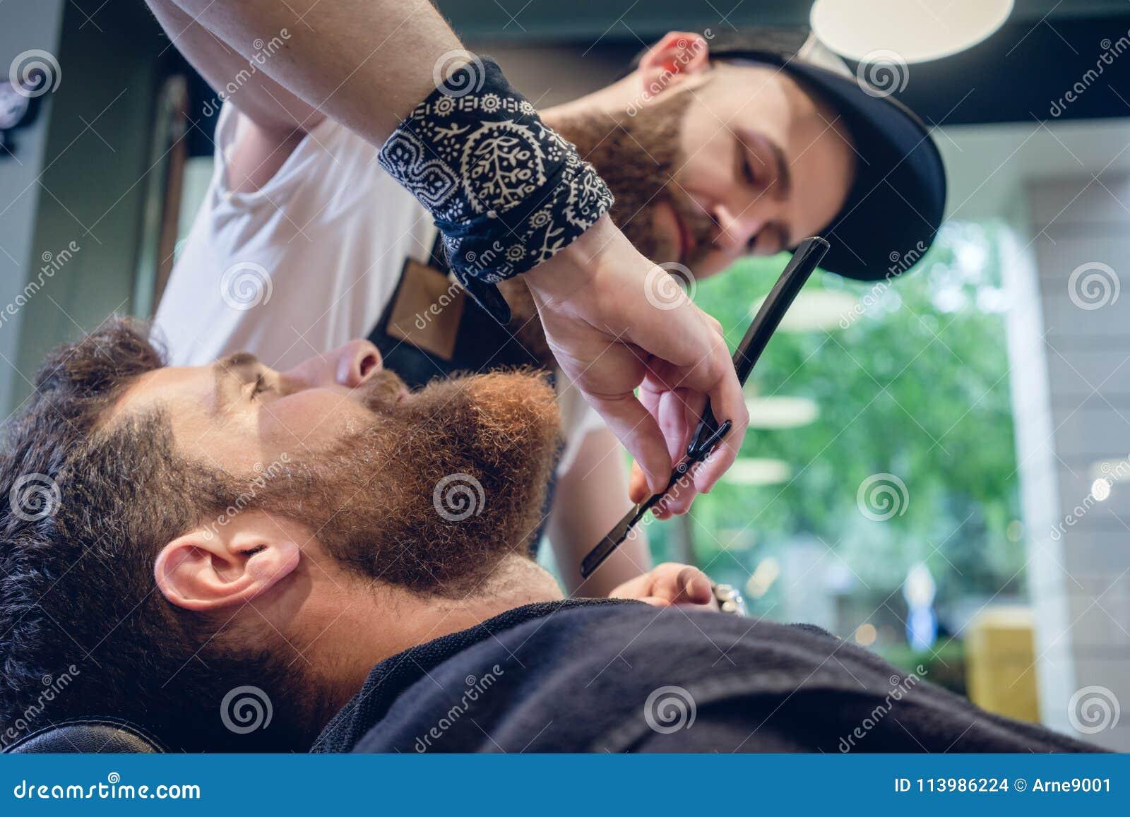 Bärtiger junger Mann bereit zum Rasieren im Friseursalon eines erfahrenen Friseurs