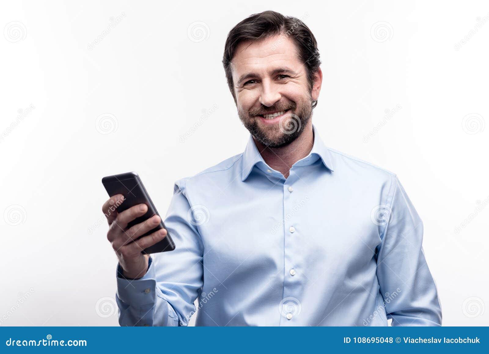 Bärtiger Mann von mittlerem Alter, der mit seinem Handy aufwirft