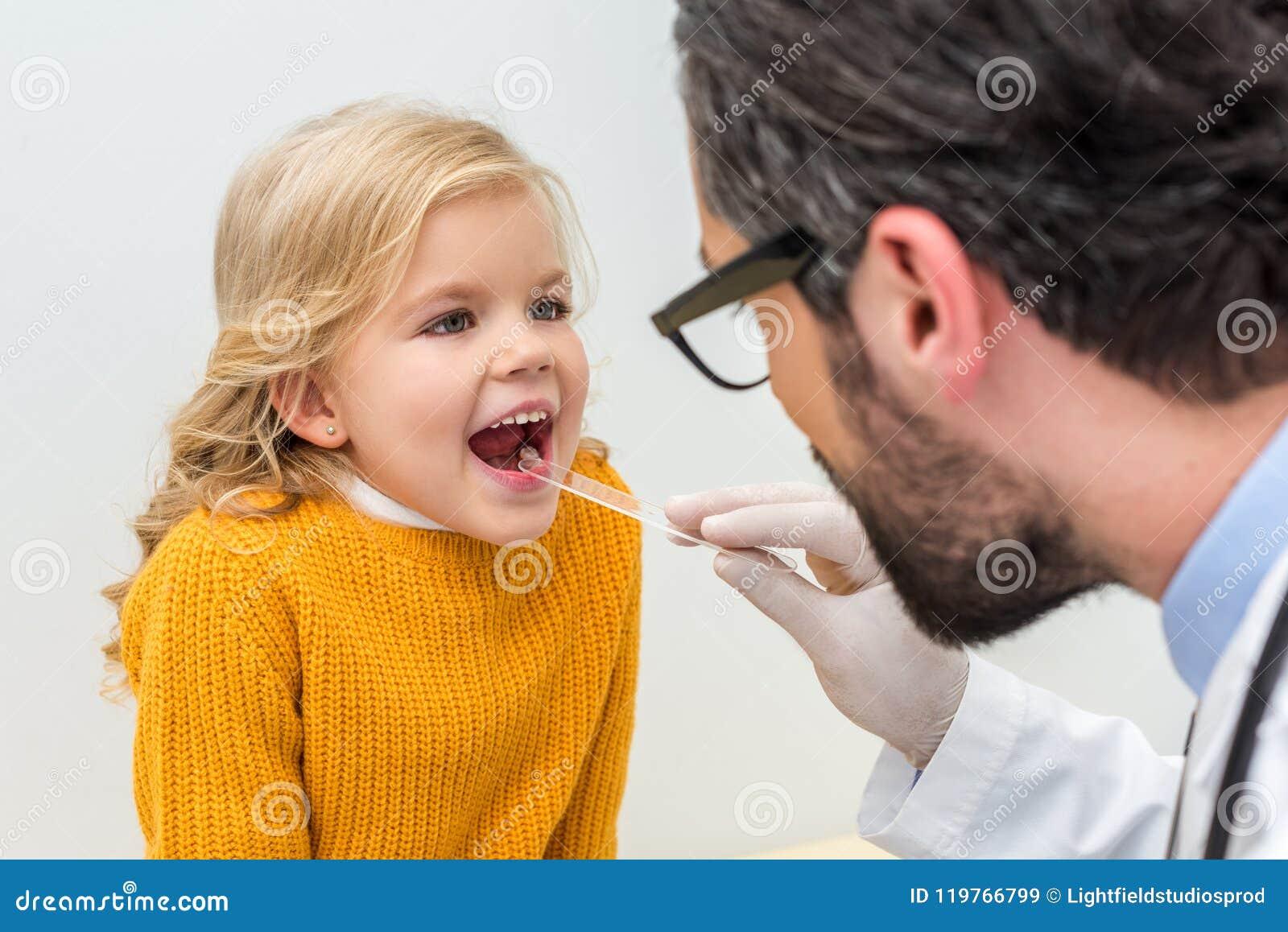 Bärtiger Pediatrist, der Kehle von entzückendem überprüft