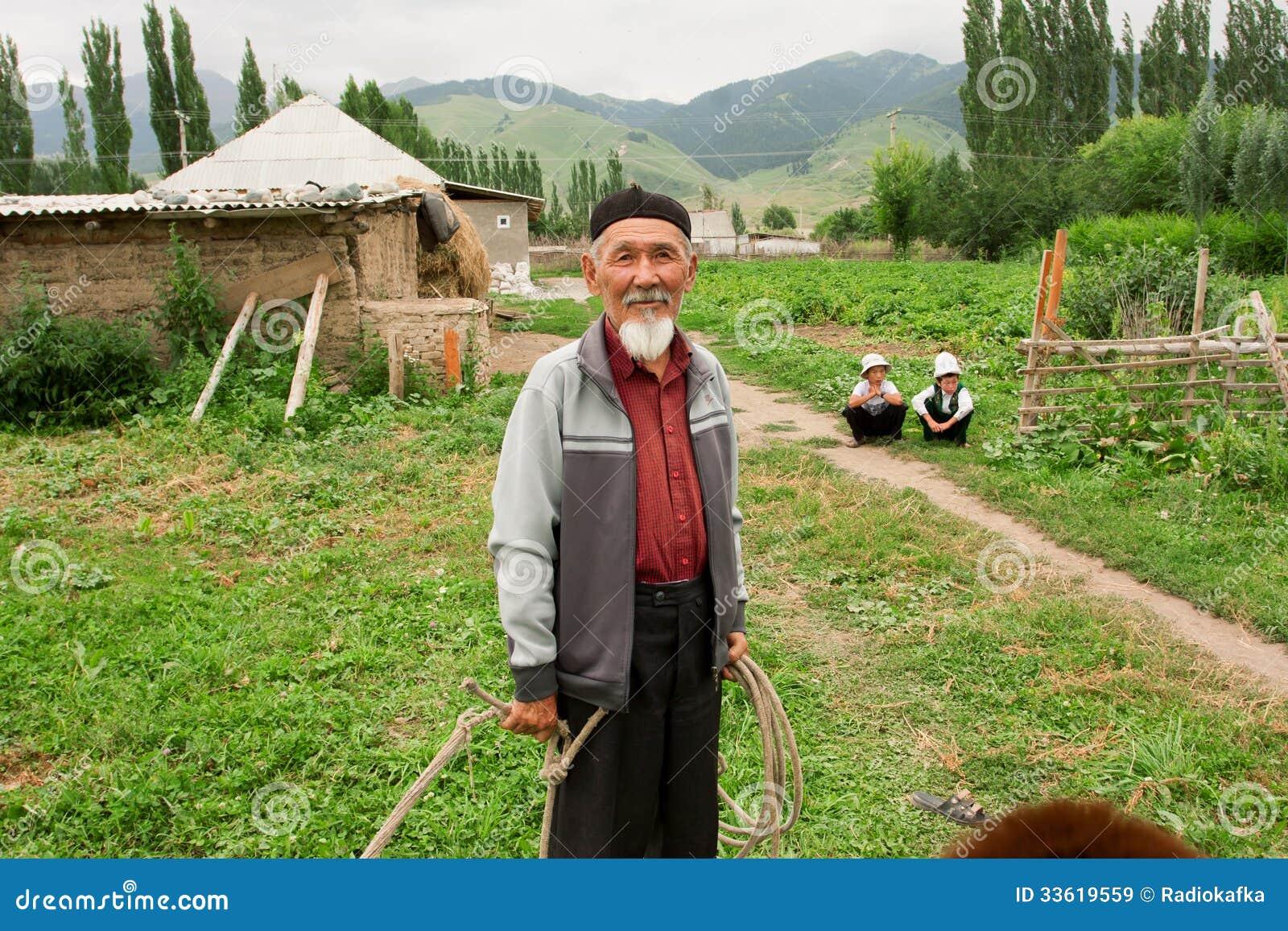 Bärtiger Senior haben Spaß mit Enkelkindern in einem Dorf Kirgisistan