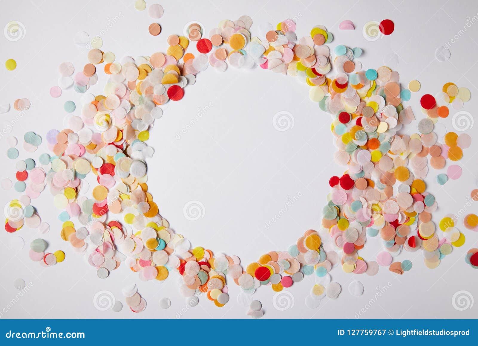 Bästa sikt av cirkeln av kulöra konfettistycken på vit yttersida