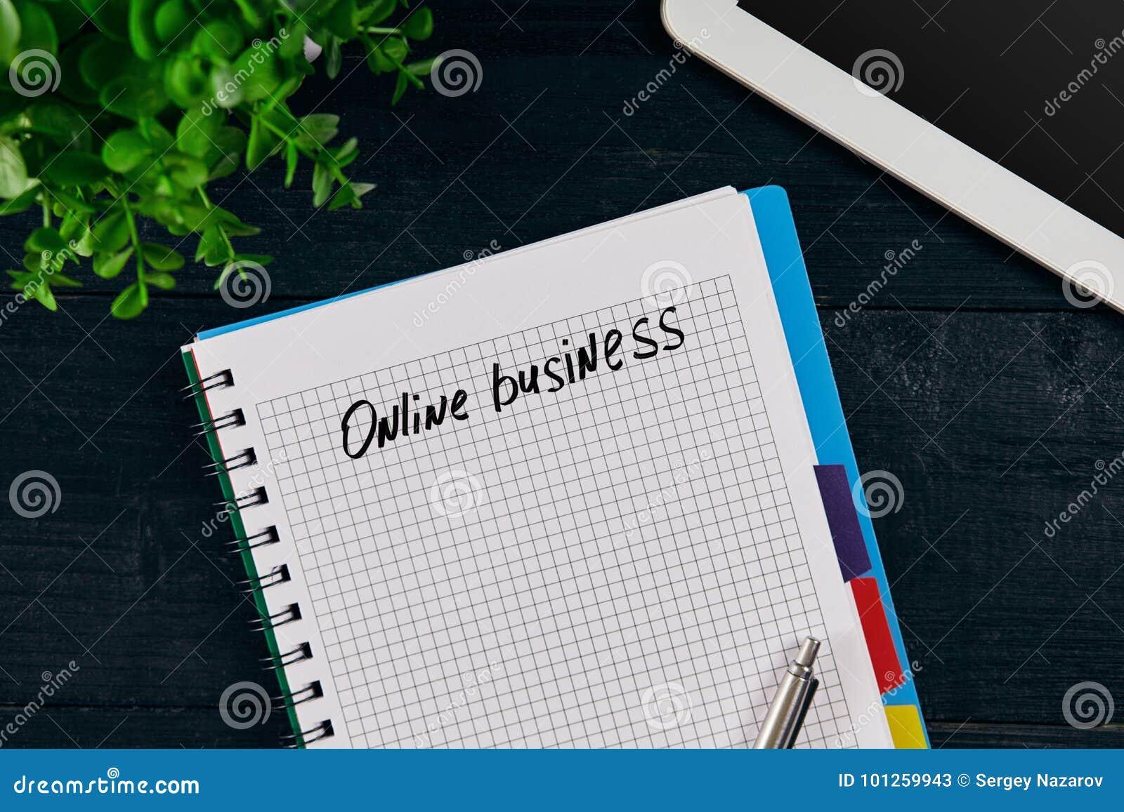 Bästa sikt av den öppna anteckningsboken som är skriftlig med ONLINE-AFFÄRSinskriften Grön blomma, minnestavla, penna och anteckn