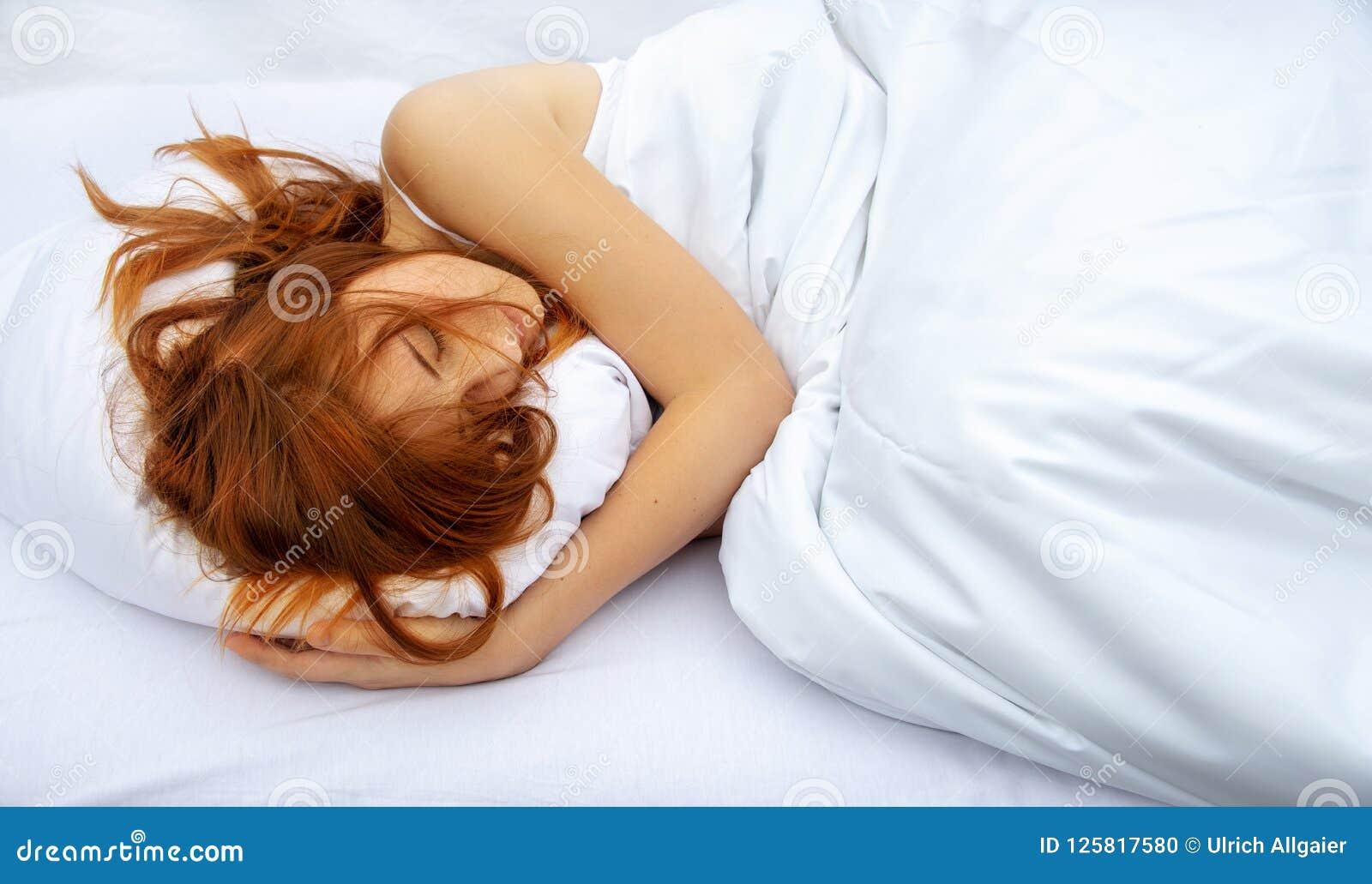 Bästa sikt av den attraktiva, unga rödhåriga kvinnan som kopplar av i säng som kramar en mjuk vit kudde som sover
