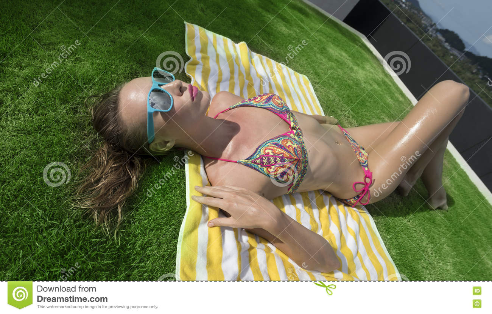 Bästa sikt av den sexiga kvinnan i bikini- och blåttsolglasögon som ligger på den randiga strandhandduken över bakgrund för grönt
