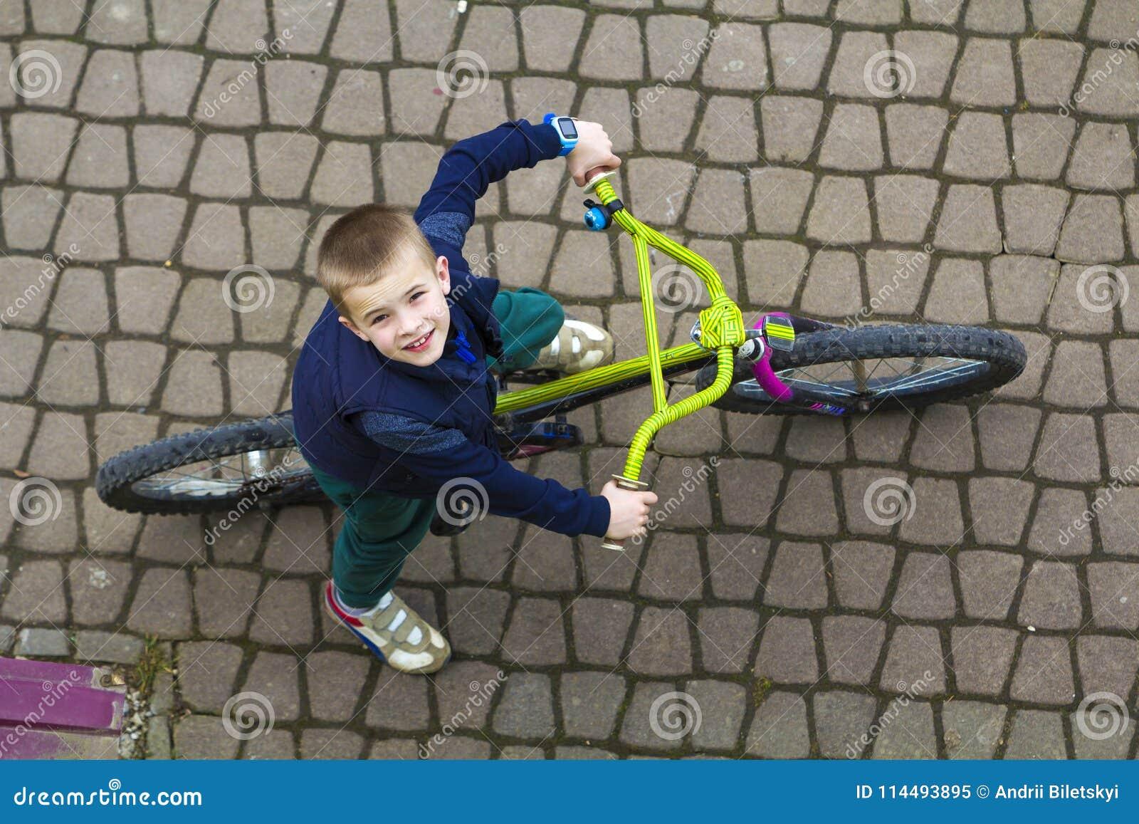 Bästa sikt av den stiliga unga le pojken som rider en cykel på den kalla vårdagen som uppåt ser Utomhus aktiviteter sund livsstil