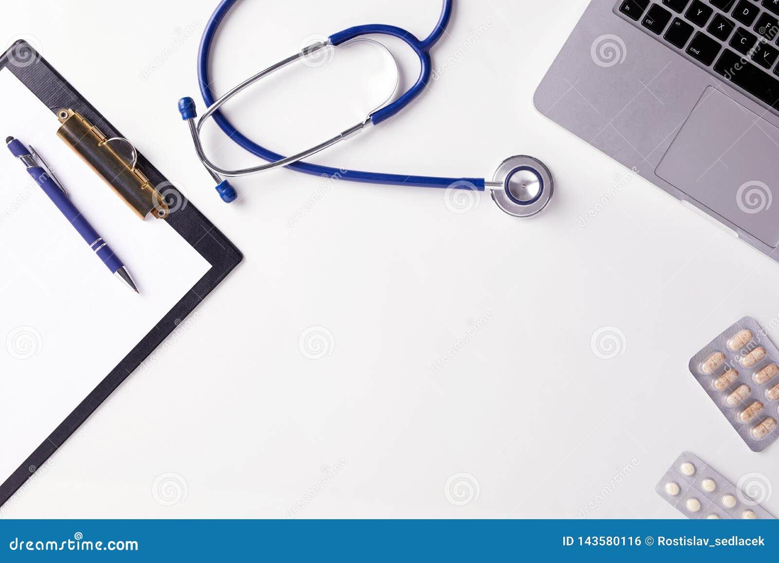 Bästa sikt av doktorsskrivbordet med stetoskopet, latptop, piller och tomt papper på skrivplattan med kopieringsutrymme