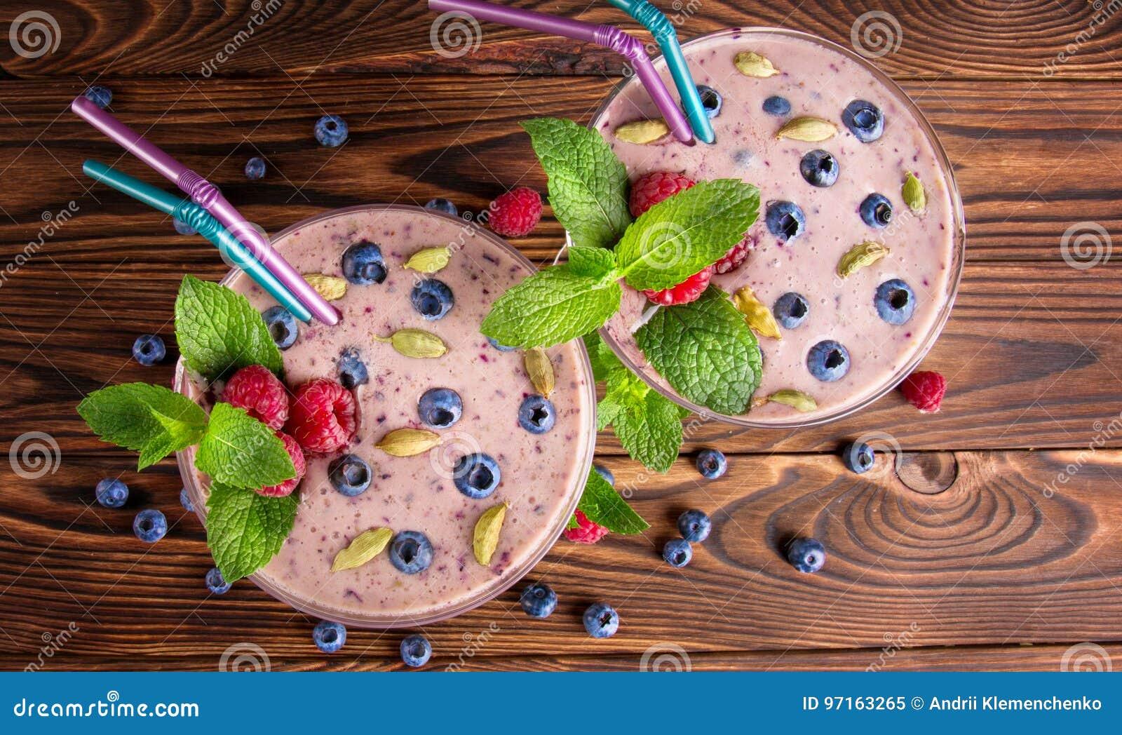 Bästa sikt av en rosa smoothie En närbild av en söt yoghurt på en träbakgrund Smoothie med hallon, blåbär och mintkaramellen