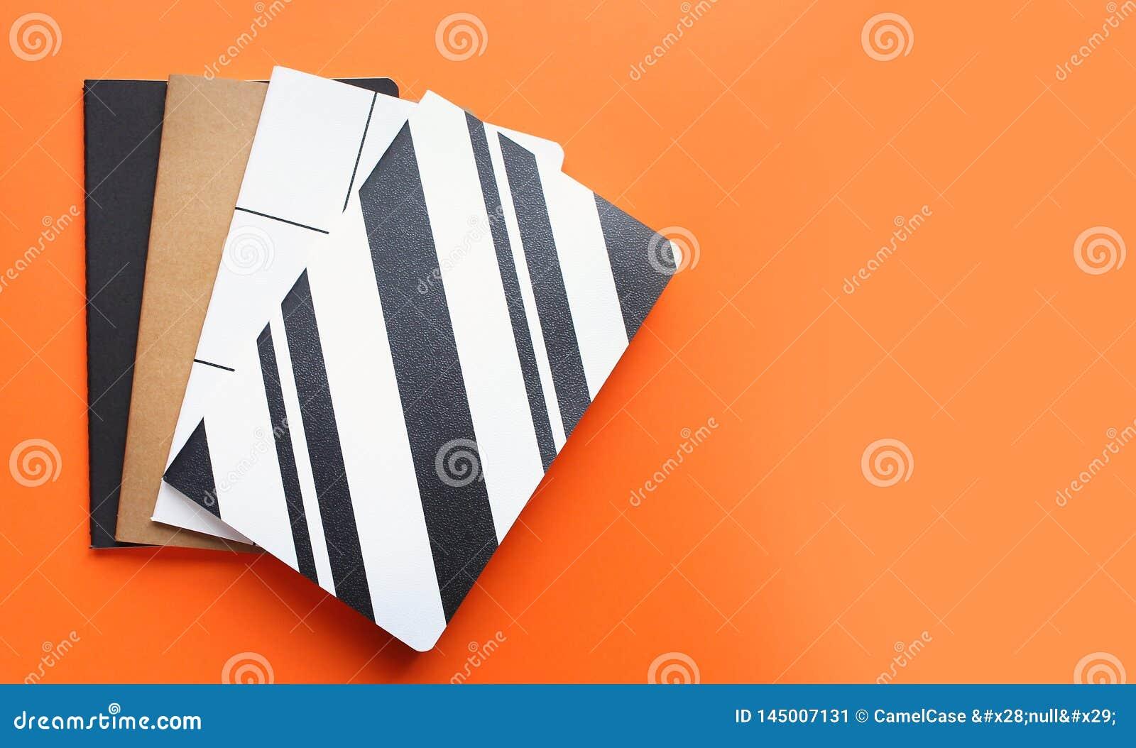 Bästa sikt av färgrika anteckningsböcker på ljus orange bakgrund