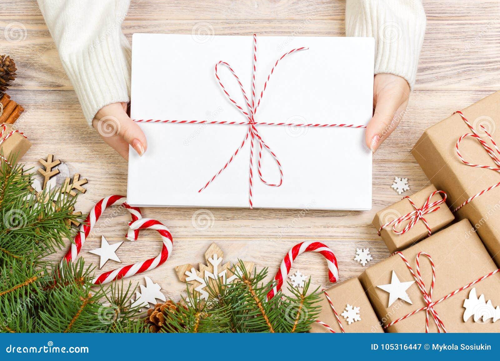Bästa sikt av julbokstaven i hand Stäng sig upp av händer som rymmer tom wishlist på trätabellen med xmas-garnering