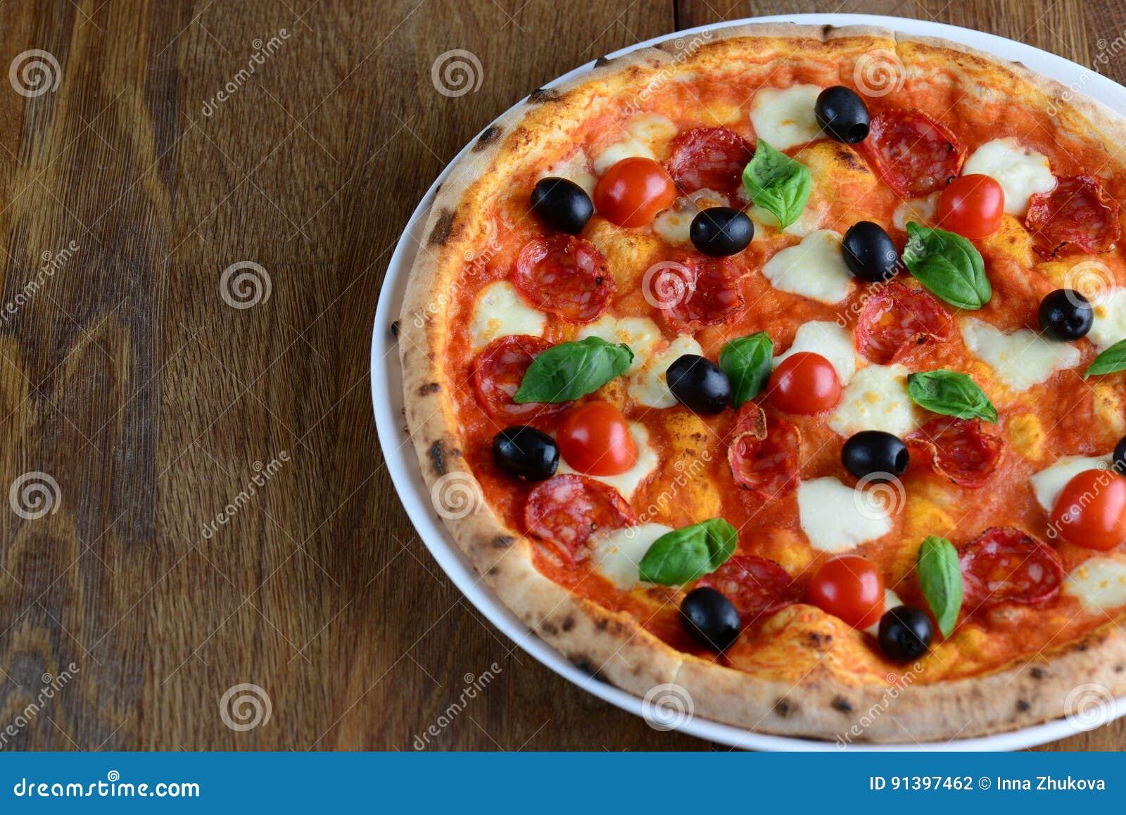Bästa sikt av neapolitan pizza med peperonin, mozzarellaen, körsbärsröda tomater och svarta oliv på en trätabell close upp Makro