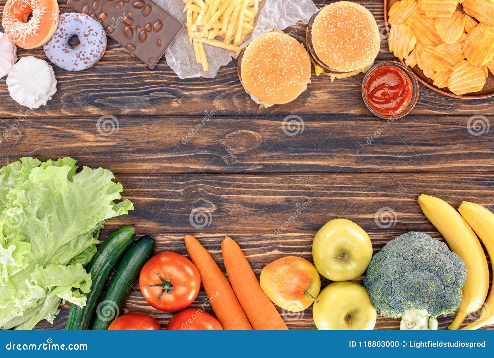 Bästa sikt av nya frukter med grönsaker och sorterad sjuklig mat på trätabellen