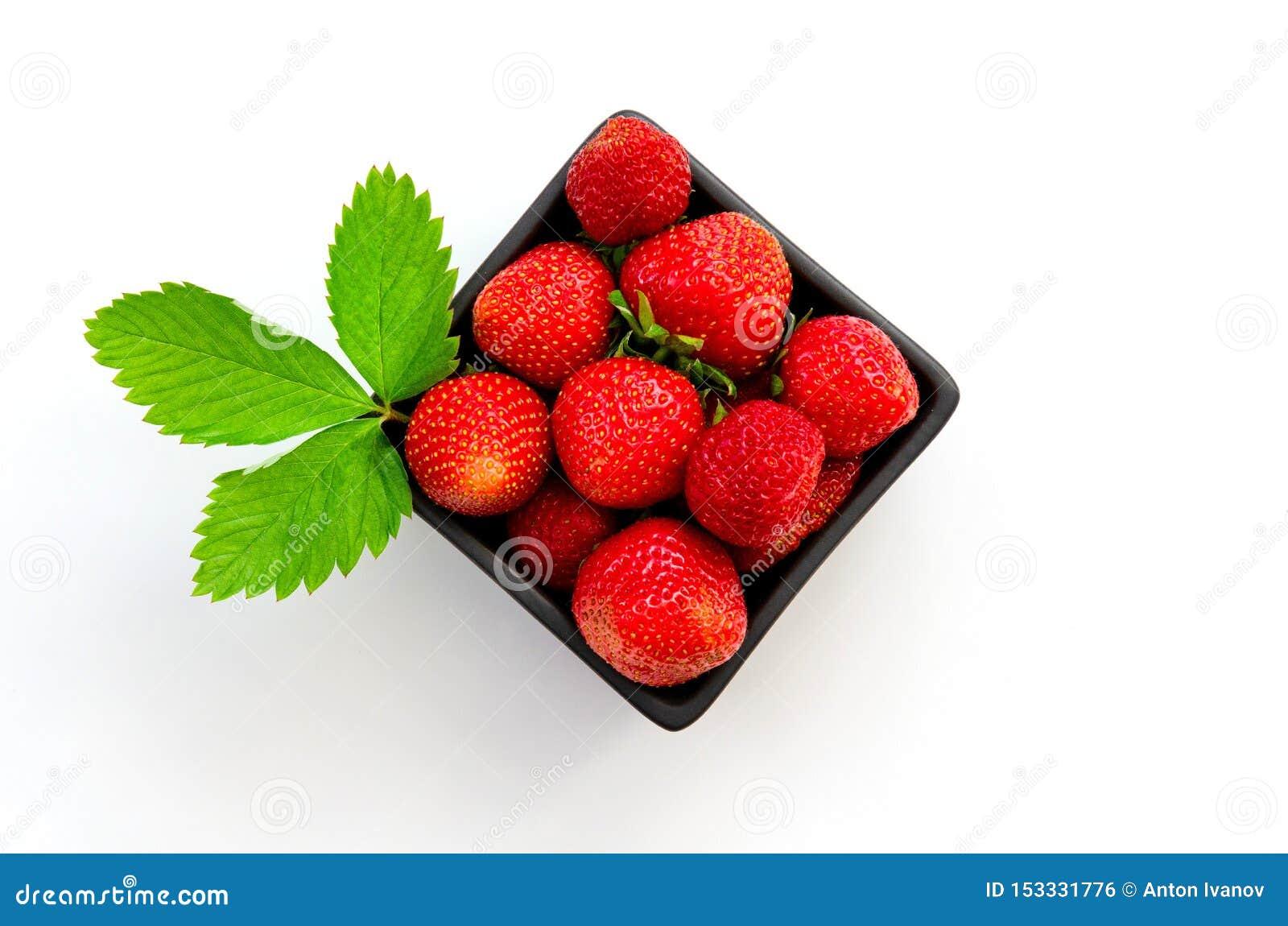 Bästa sikt av smakliga spanska jordgubbar som samlas nytt på en ask som isoleras på vit bakgrund