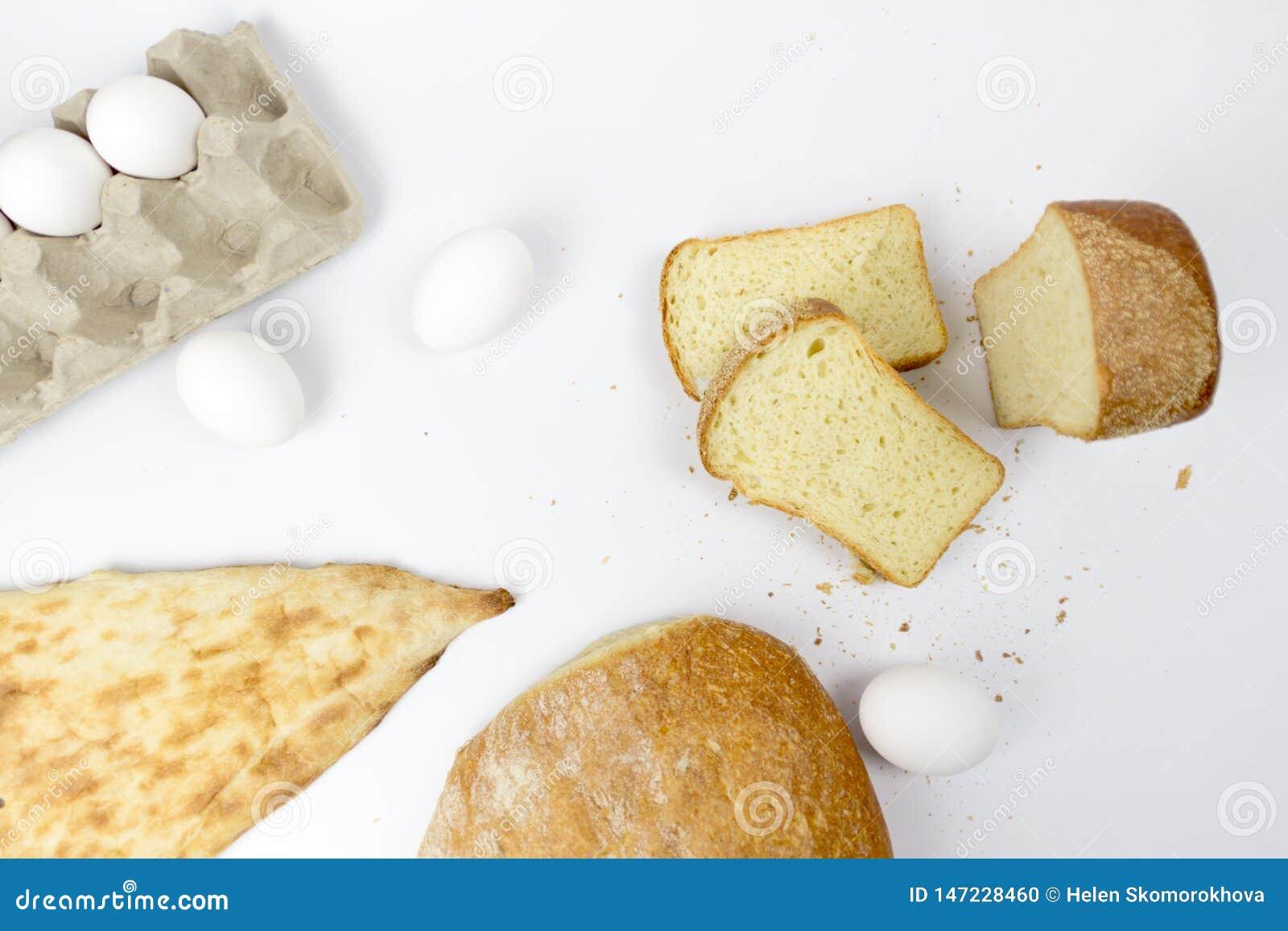 Bästa sikt av sortimentet av den olika sorten av det sädes- bagerit: bröd giffel, bullar som isoleras på vit, woodden bakgrund