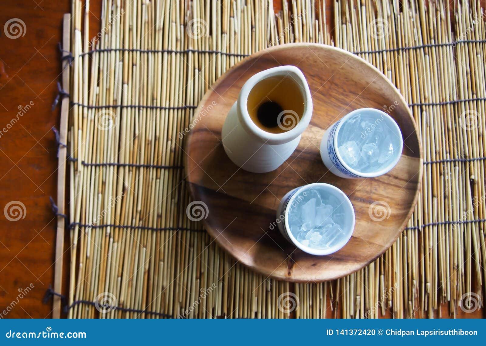 Bästa sikt av tekrukan och exponeringsglas av med is te På en träplatta, som förläggas på en matt bambu och på en tabell