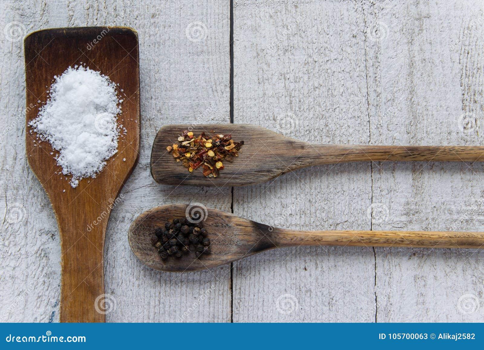 Bästa sikt av träskedar med spieces på vit träbakgrund