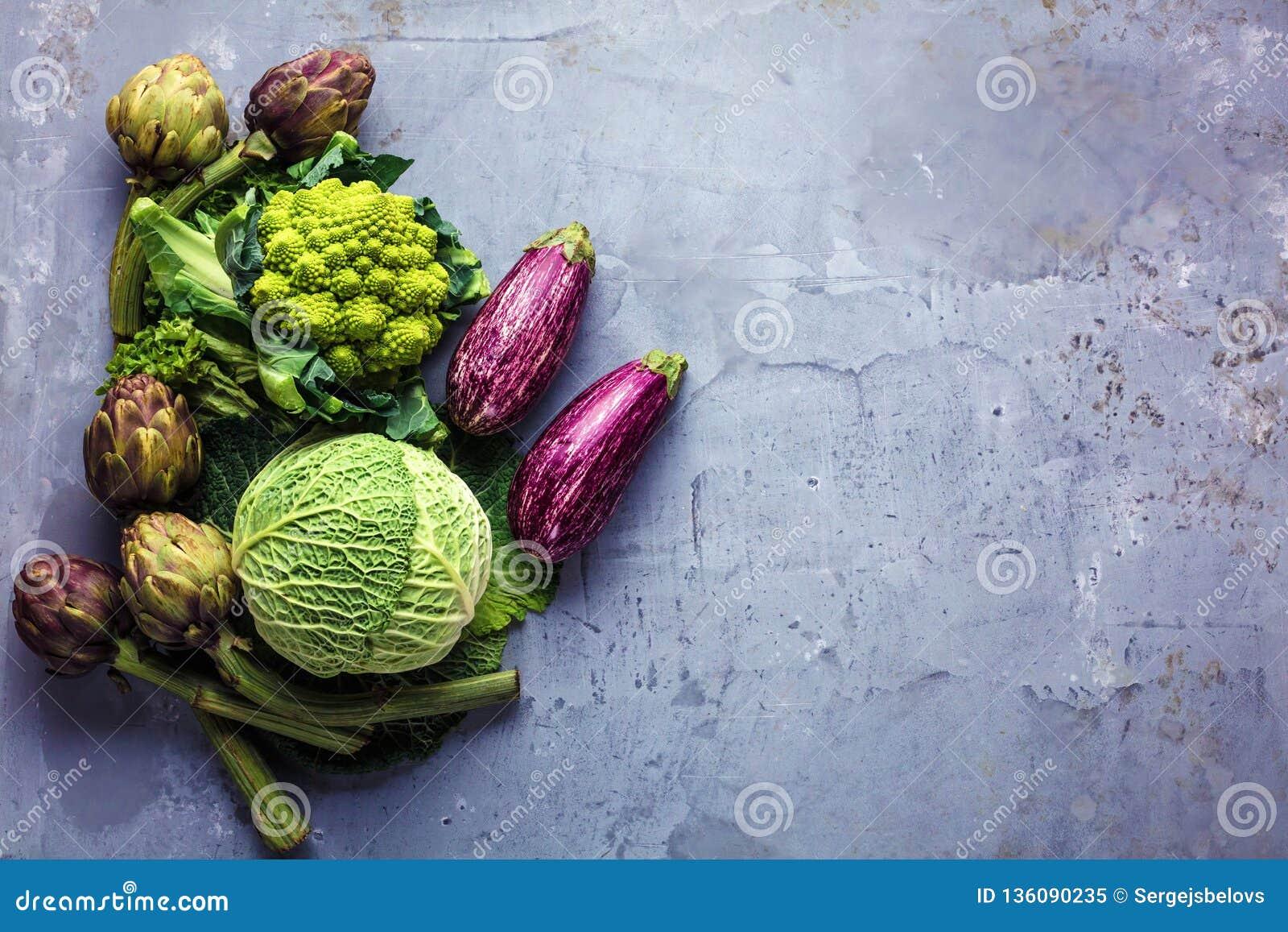 Bästa sikt på nya grönsaker som ordnas runt om gränsen på grå kökcountertop