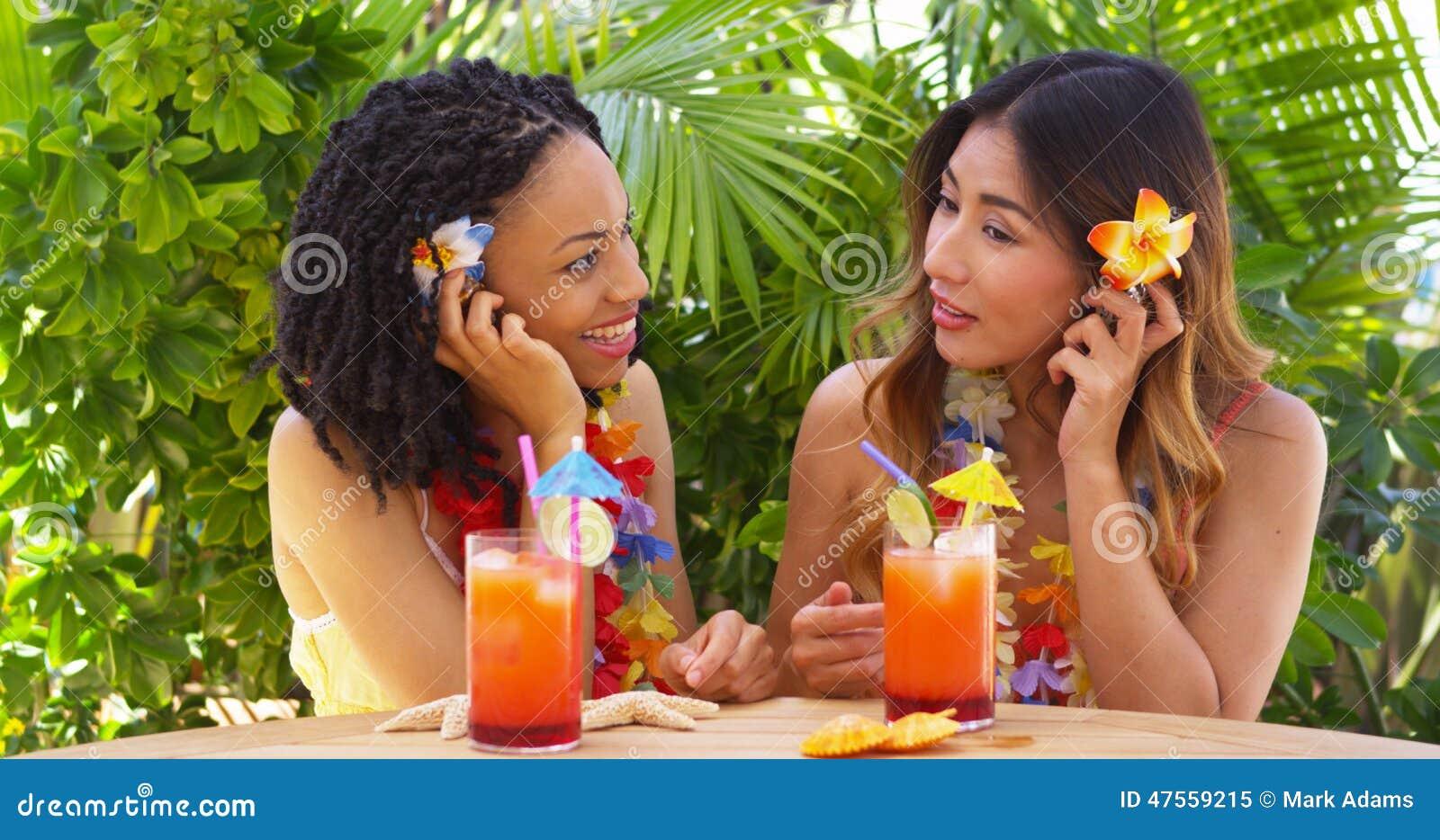 Bästa vän på semester som lyssnar till havsskal och dricker coctailar