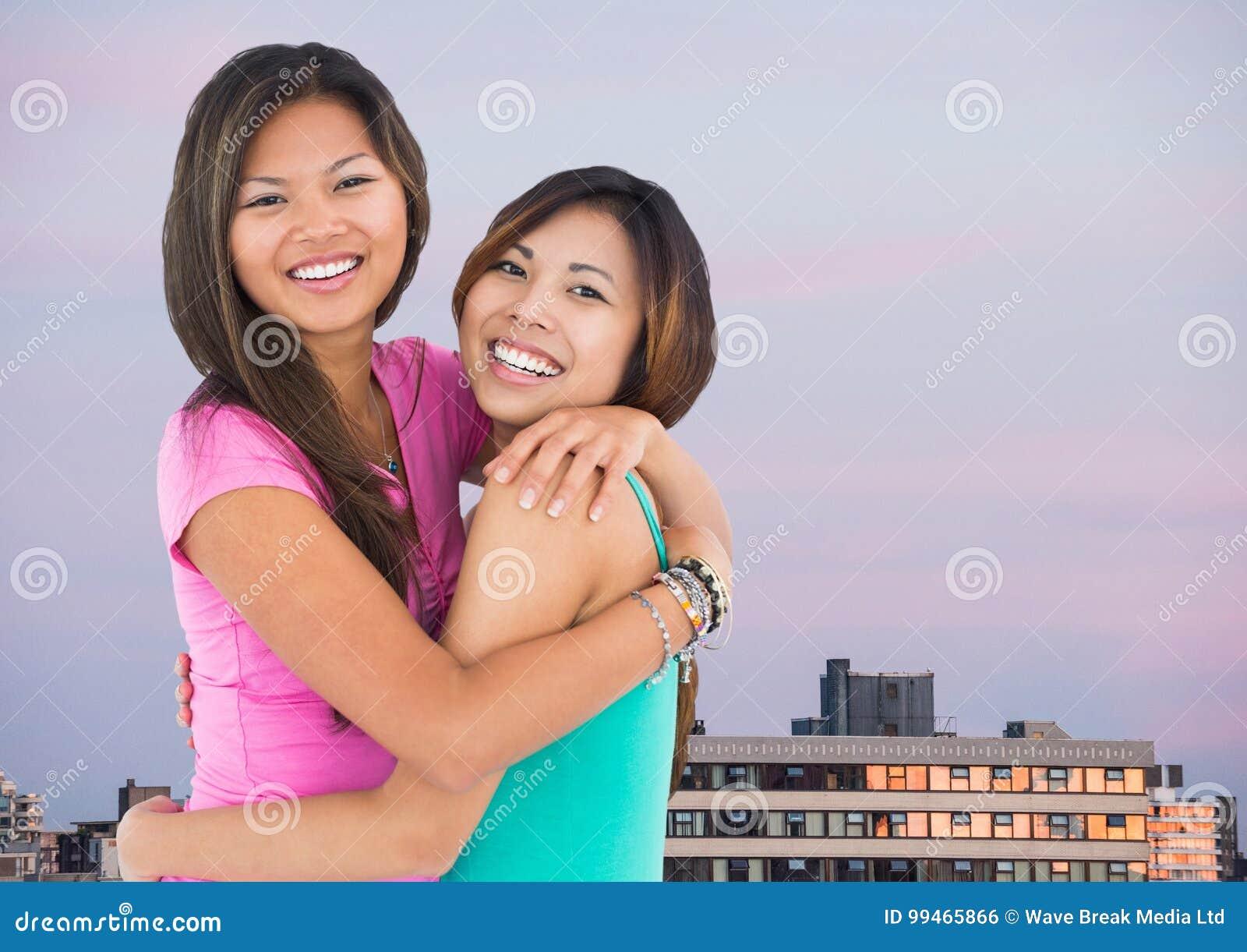 Bästa vän som kramar mot byggnader och aftonhimmel