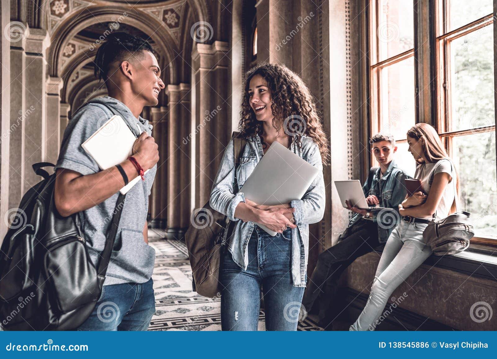 Bästa vän Unga le studenter som står i universitetkorridoren och, talar med de