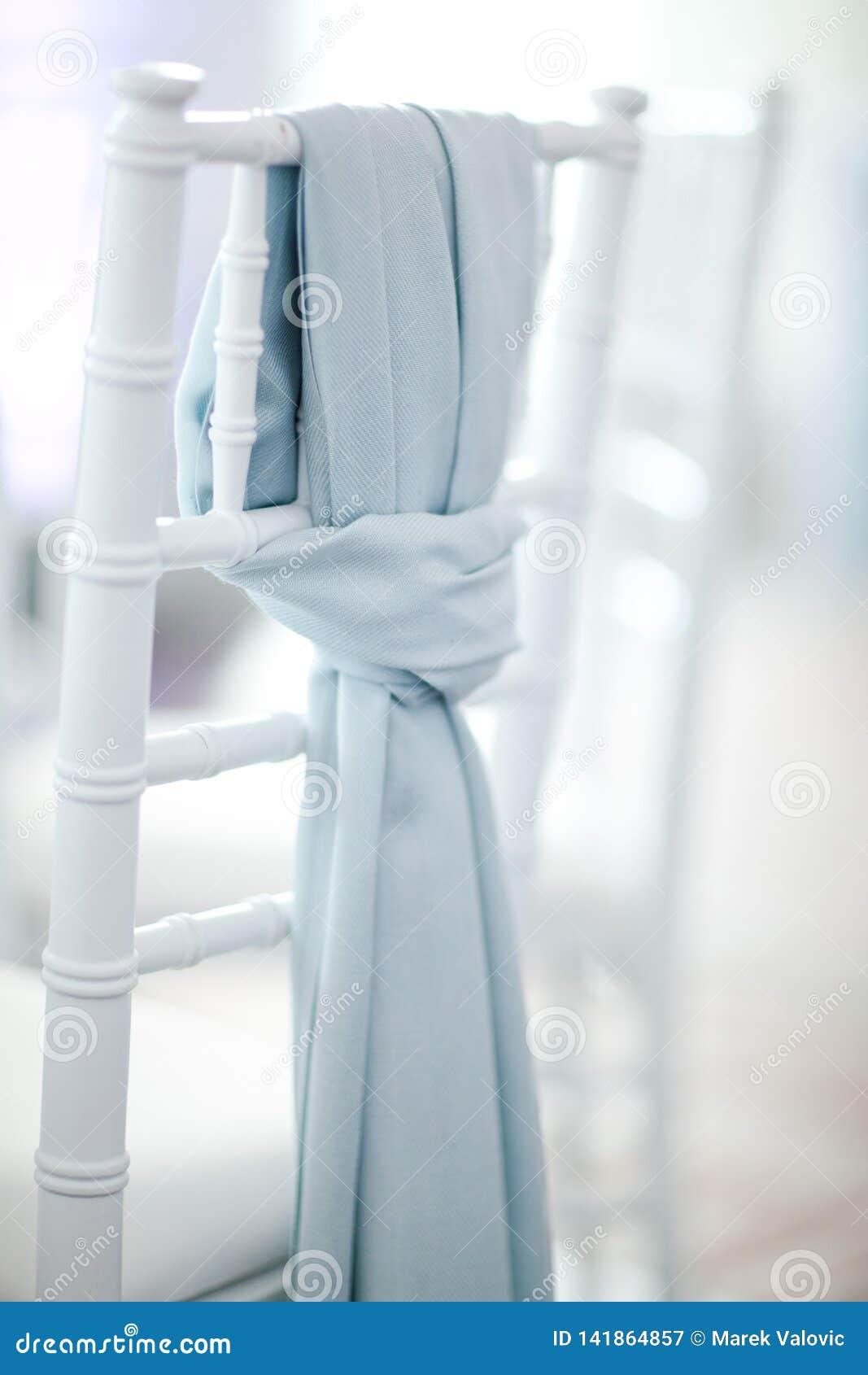 Błękitny szalik na białym ślubu krześle - Skupiającym się na szaliku