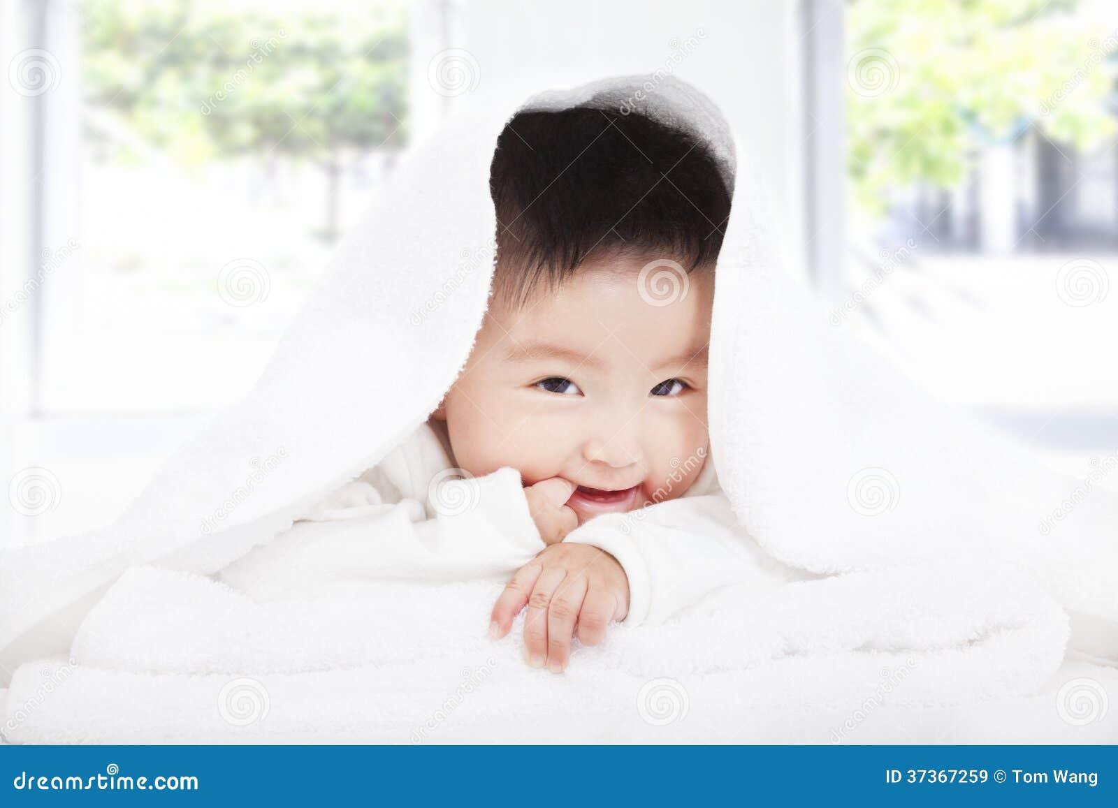 Bébé asiatique suçant le doigt sous la couverture ou la serviette