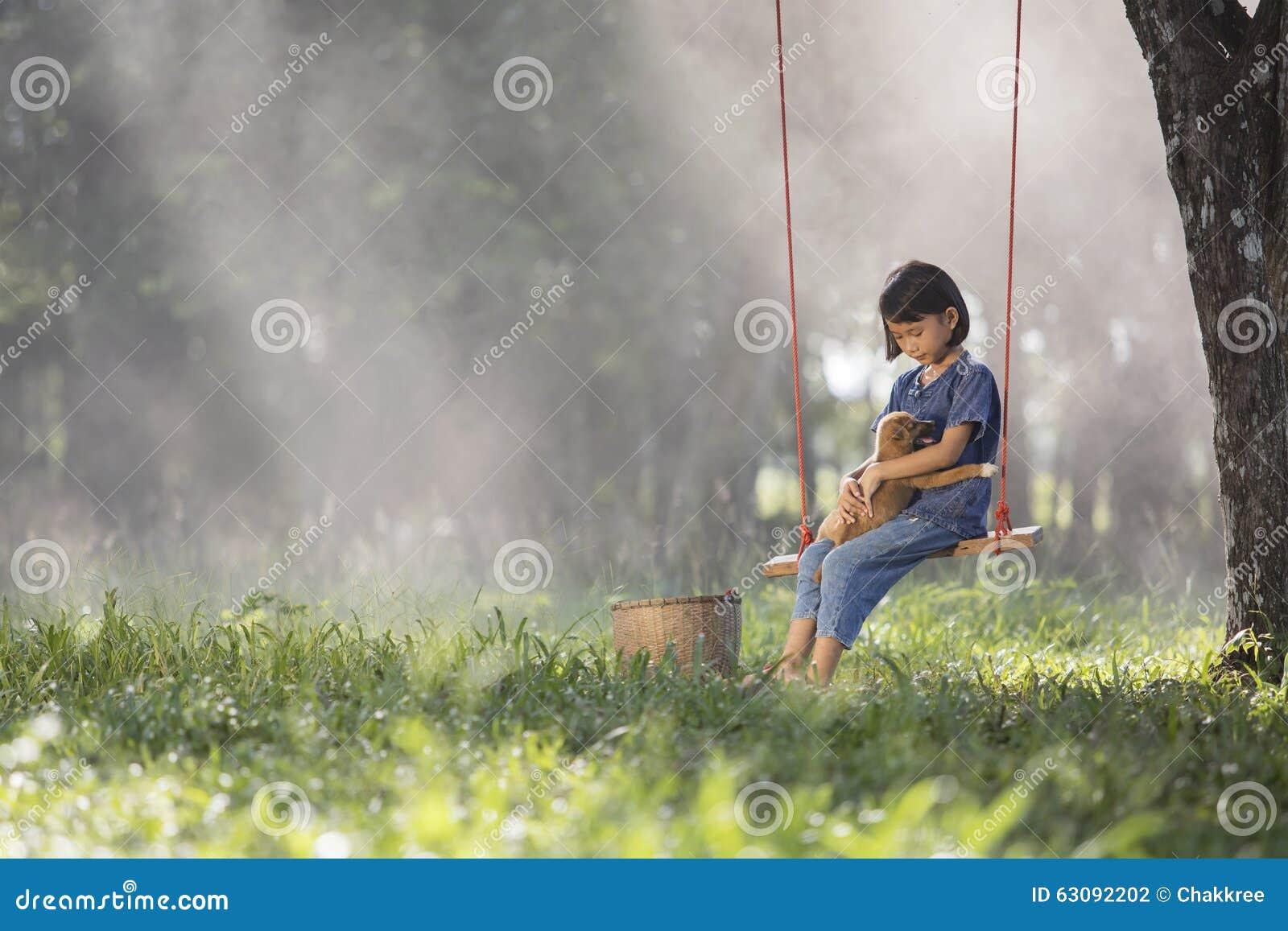 Download Bébé Asiatique Sur L'oscillation Avec Le Chiot Photo stock - Image du heureux, né: 63092202