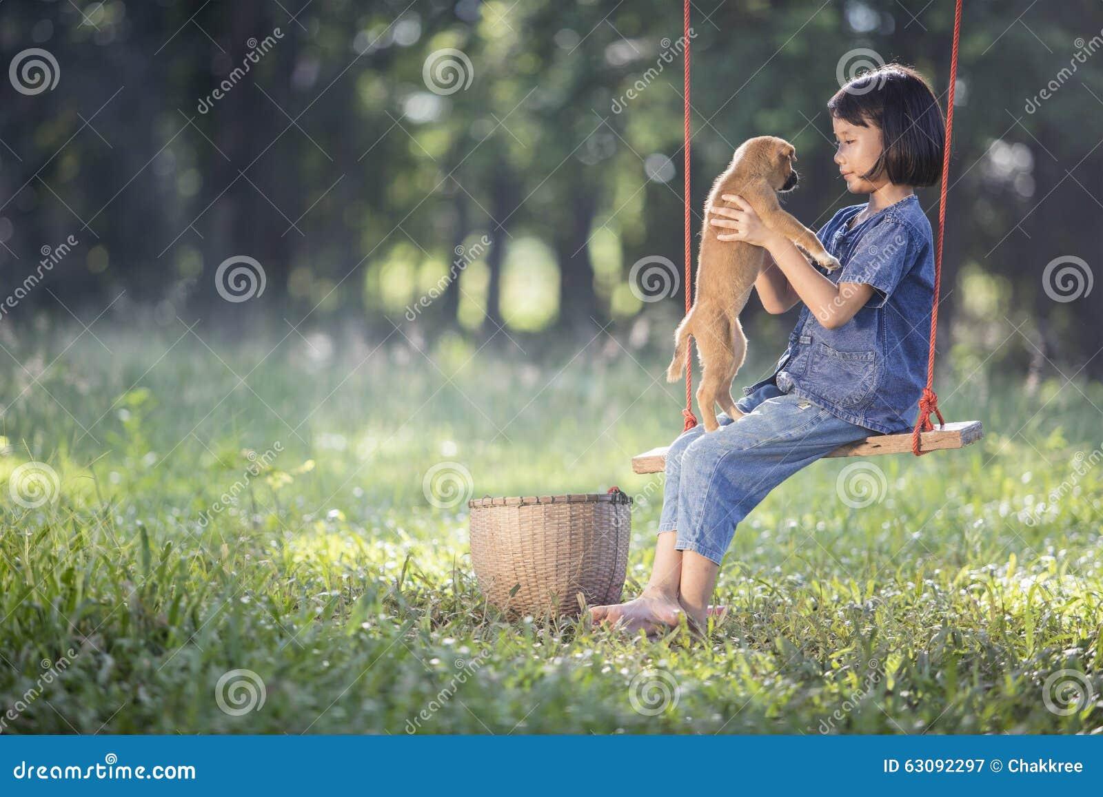 Download Bébé Asiatique Sur L'oscillation Avec Le Chiot Image stock - Image du animal, enfants: 63092297